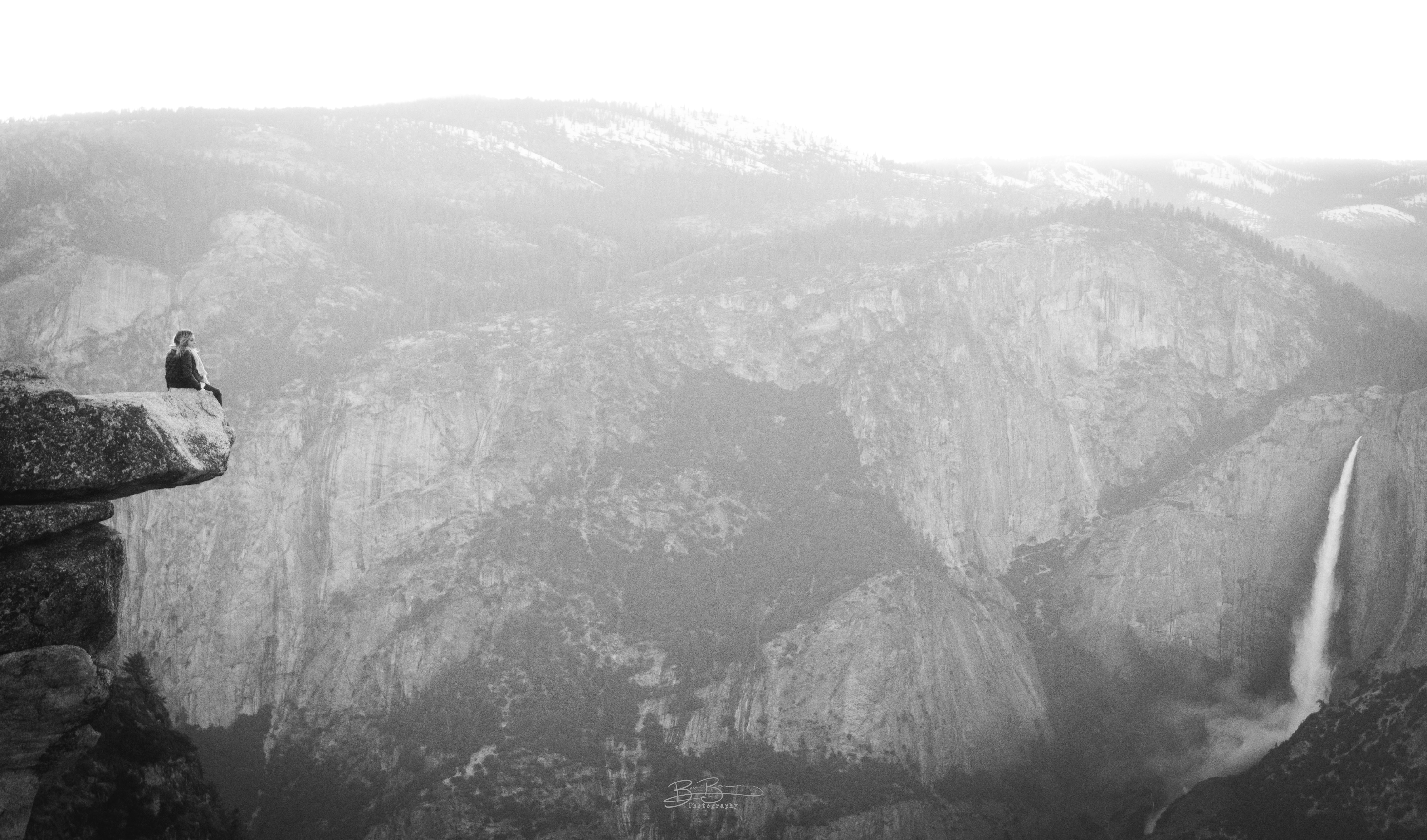 grayscale photography of person sitting on rock and waterfalls during daytime