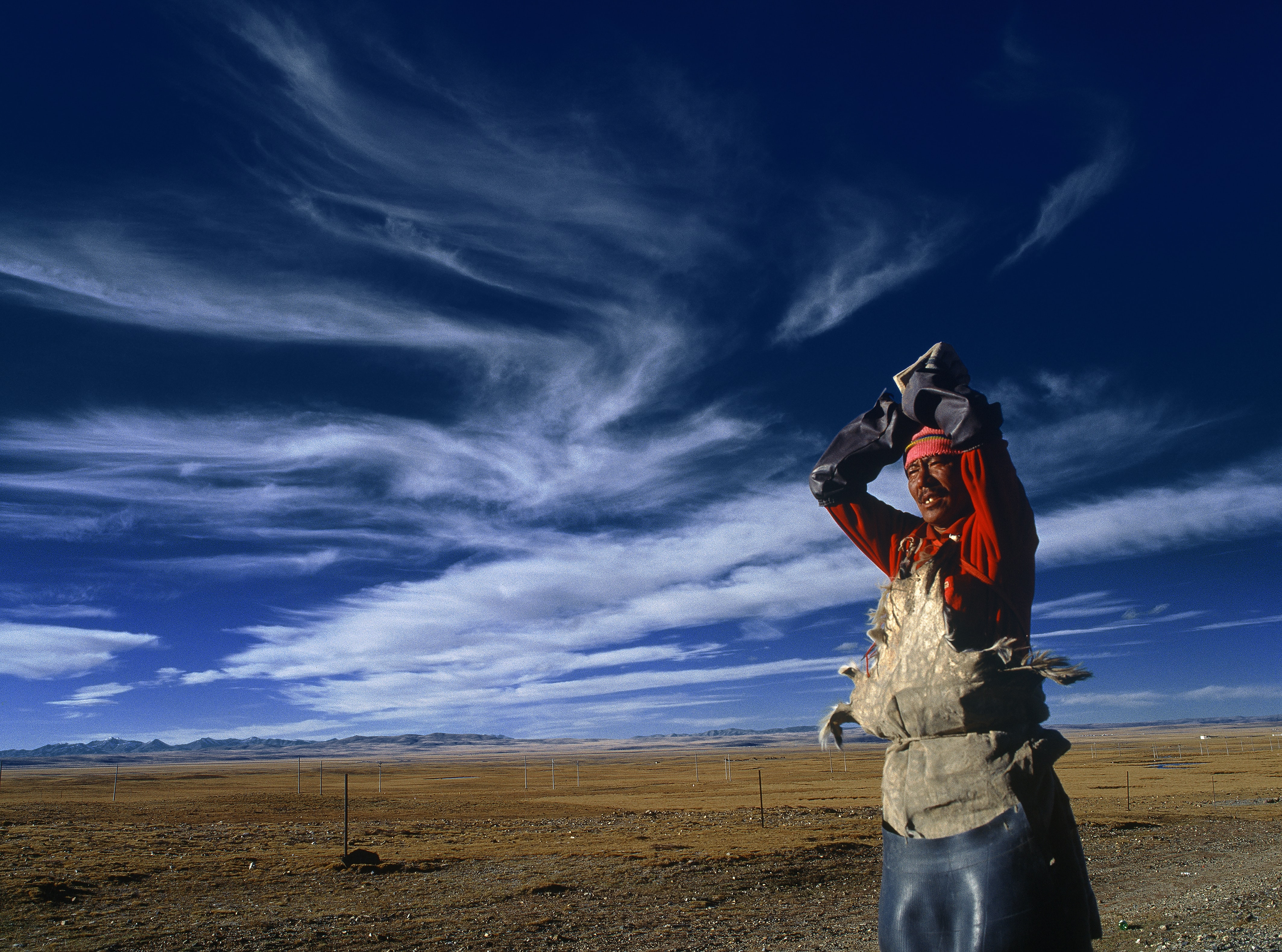 A man wearing a work apron stands in a field with a bright blue sky
