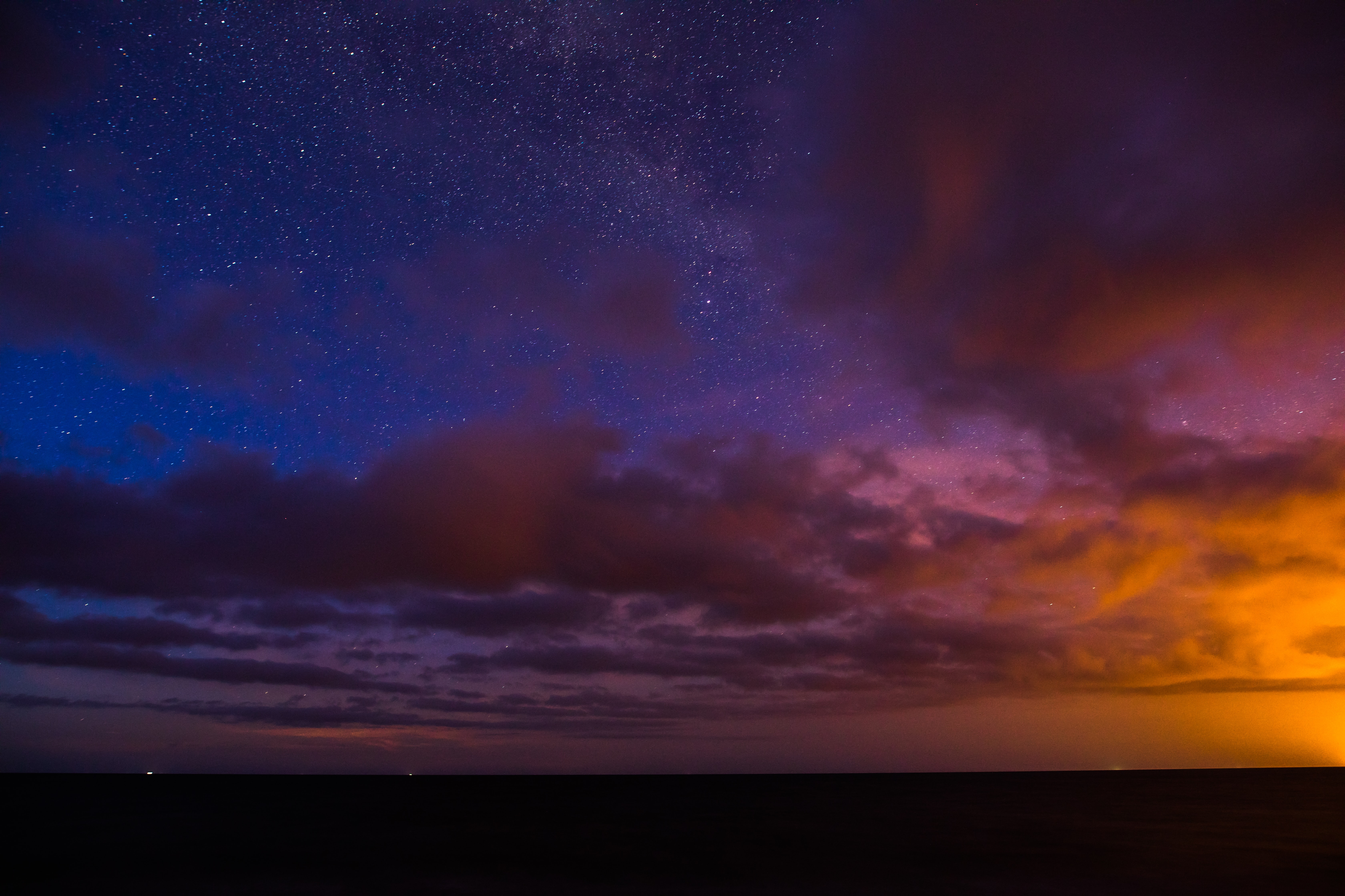 Moody deep sunset with navy, jewel purple, and orange against dark clouds at Draghanstown.