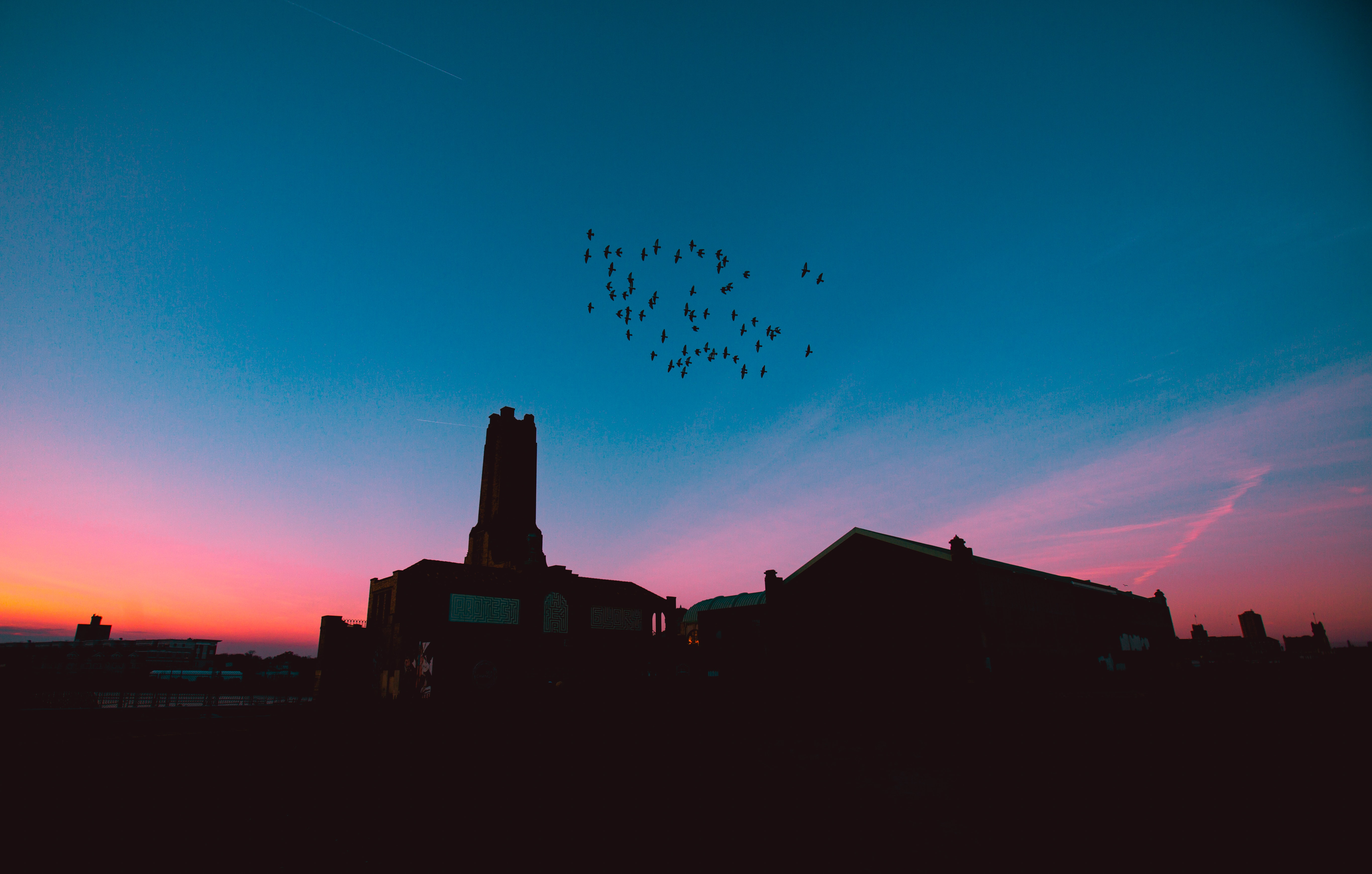 A flock of birds in silhouette over an industrial chimney during a pink and orange sunset at Ashbury Park.