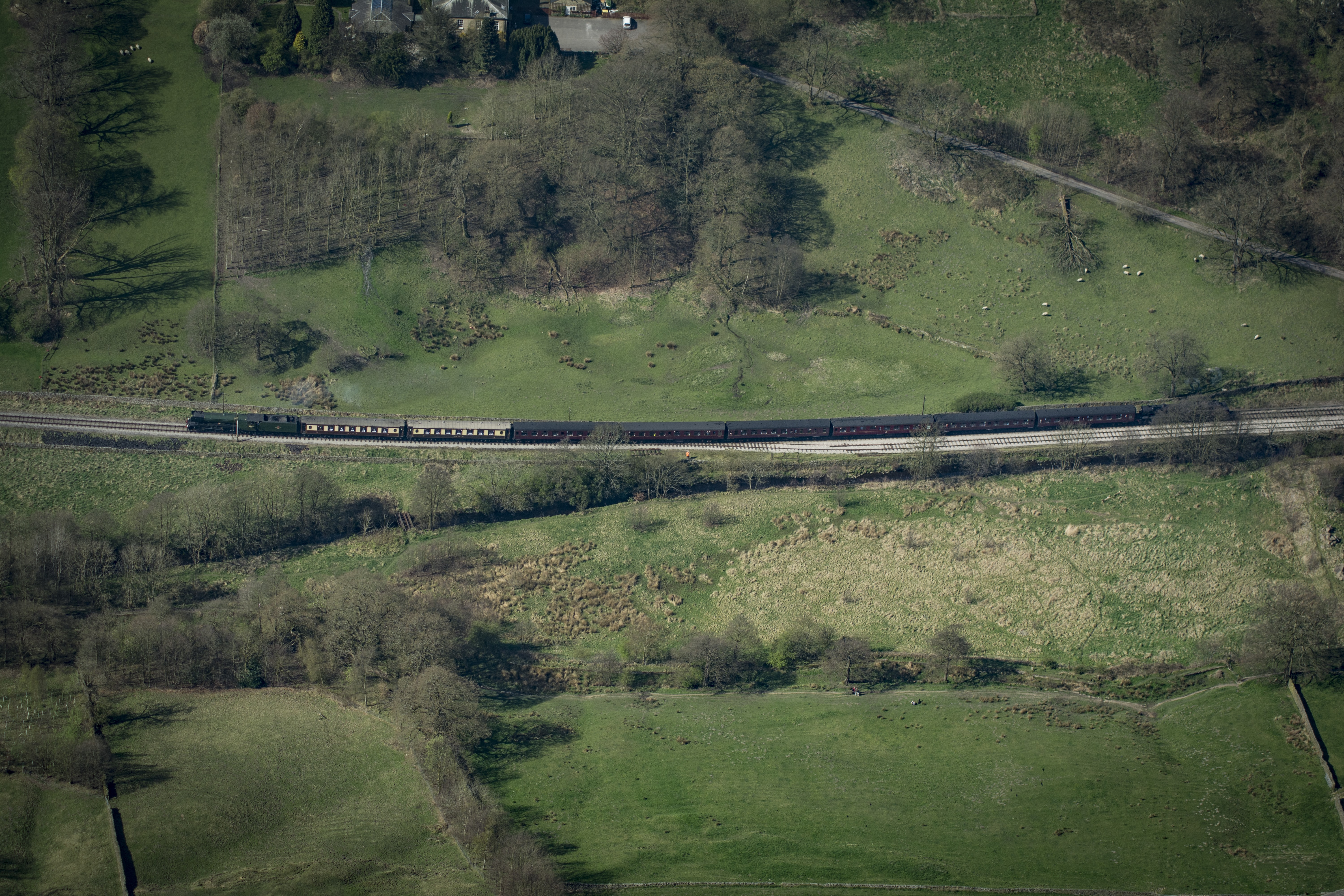 An aerial view of a train moving through a green plain