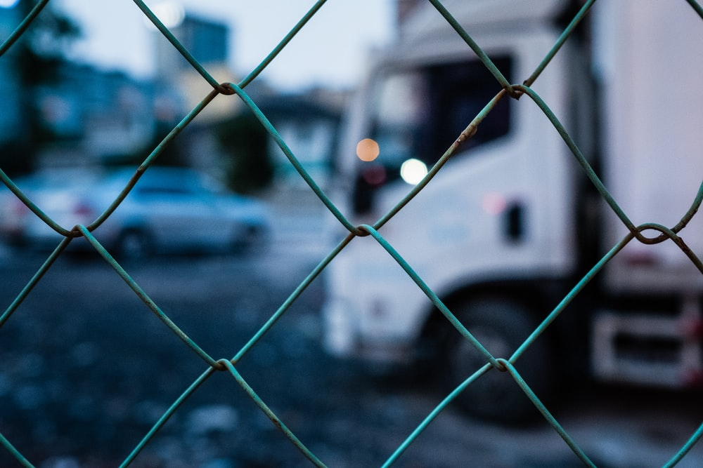 selective focus photography of gray chain link fence
