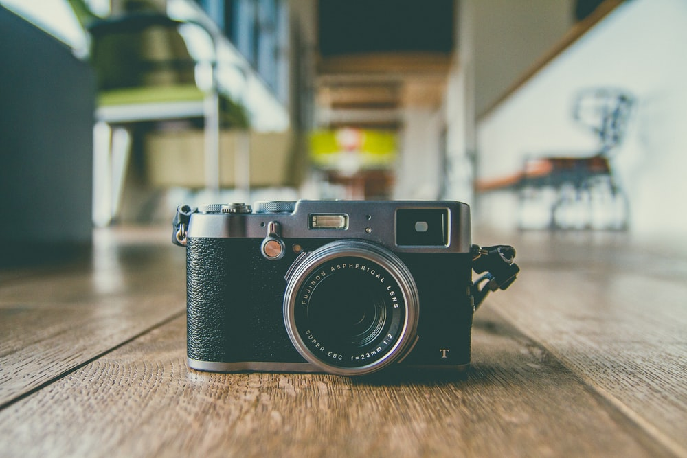 black and gray camera on brown wooden surface