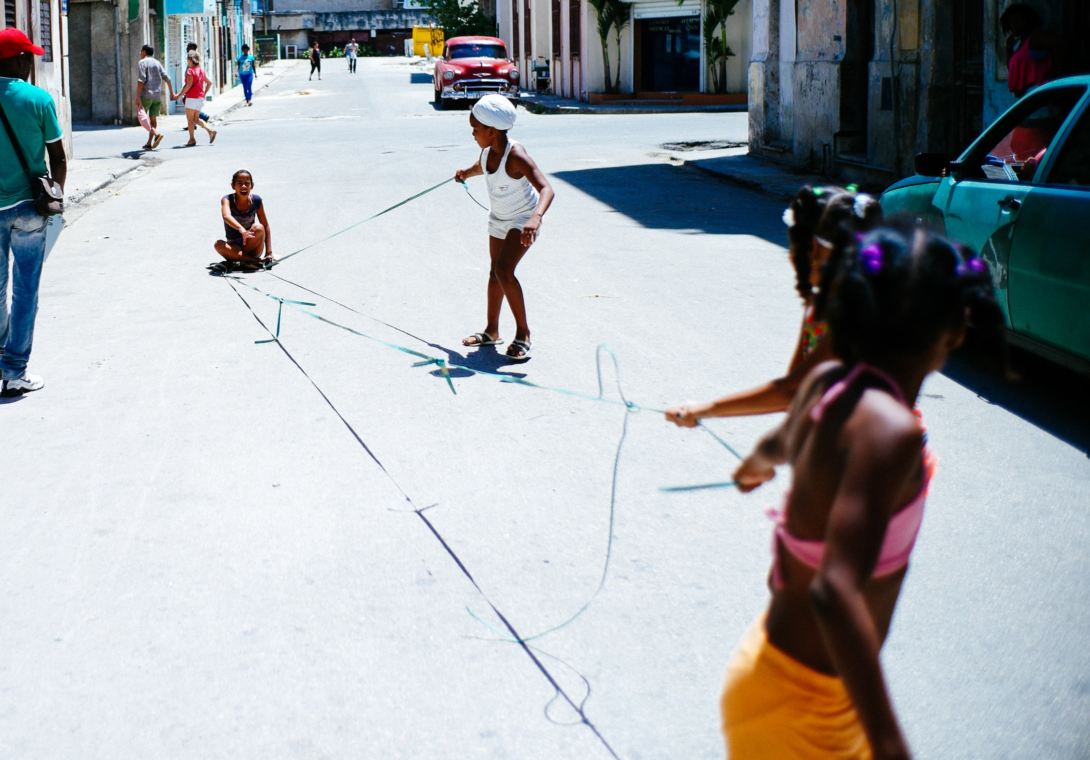 Three children playing with a string in the streets of Havana