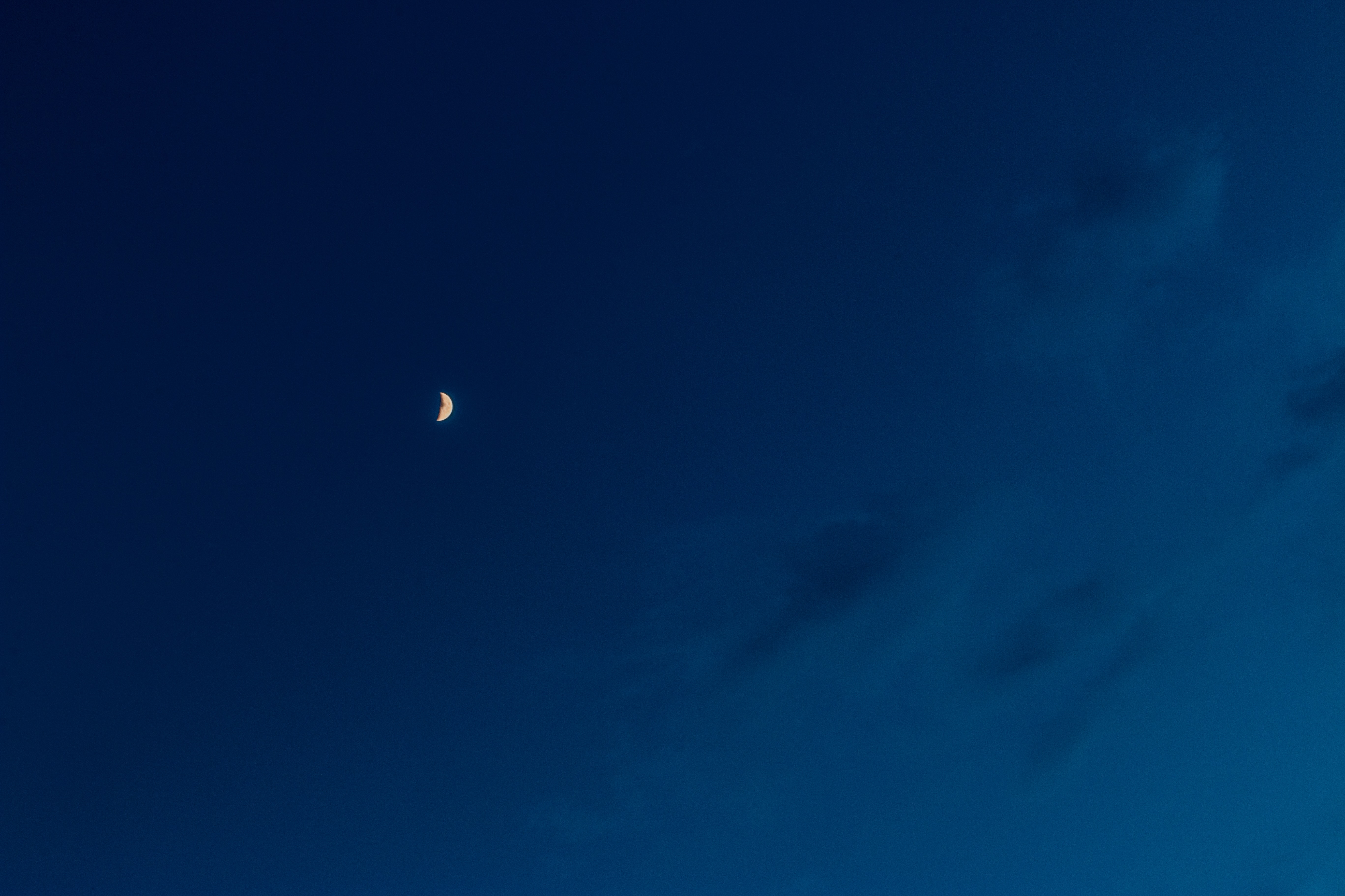 A crescent moon seen near fluffy clouds on an inky blue sky