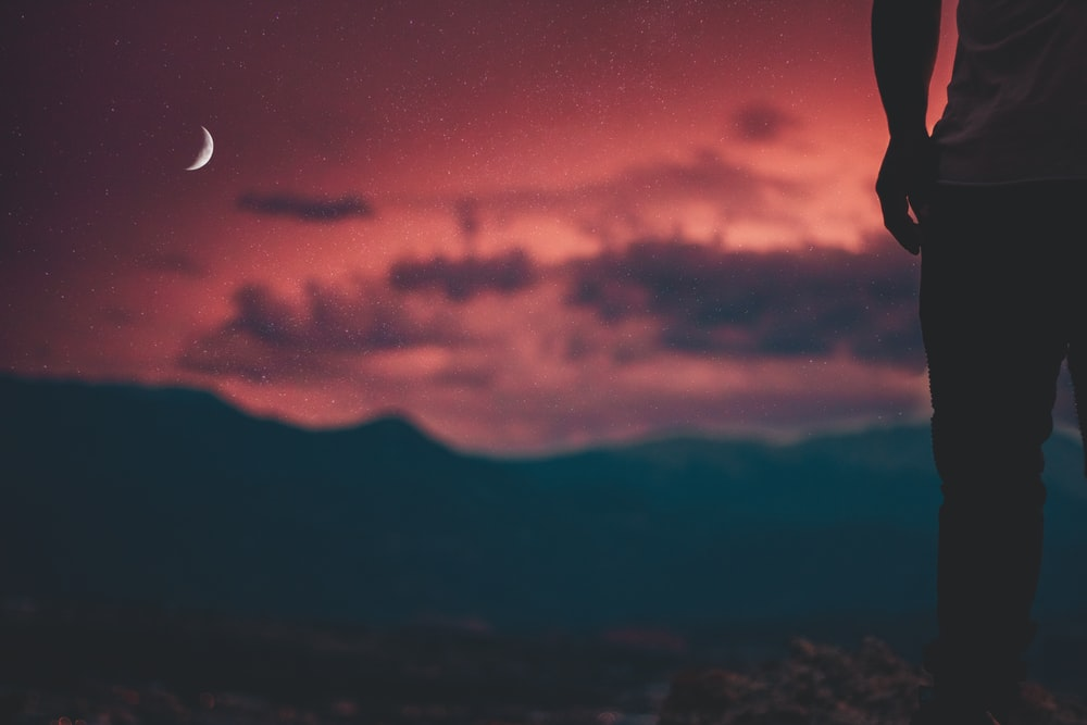 silhouette of man looking at moon