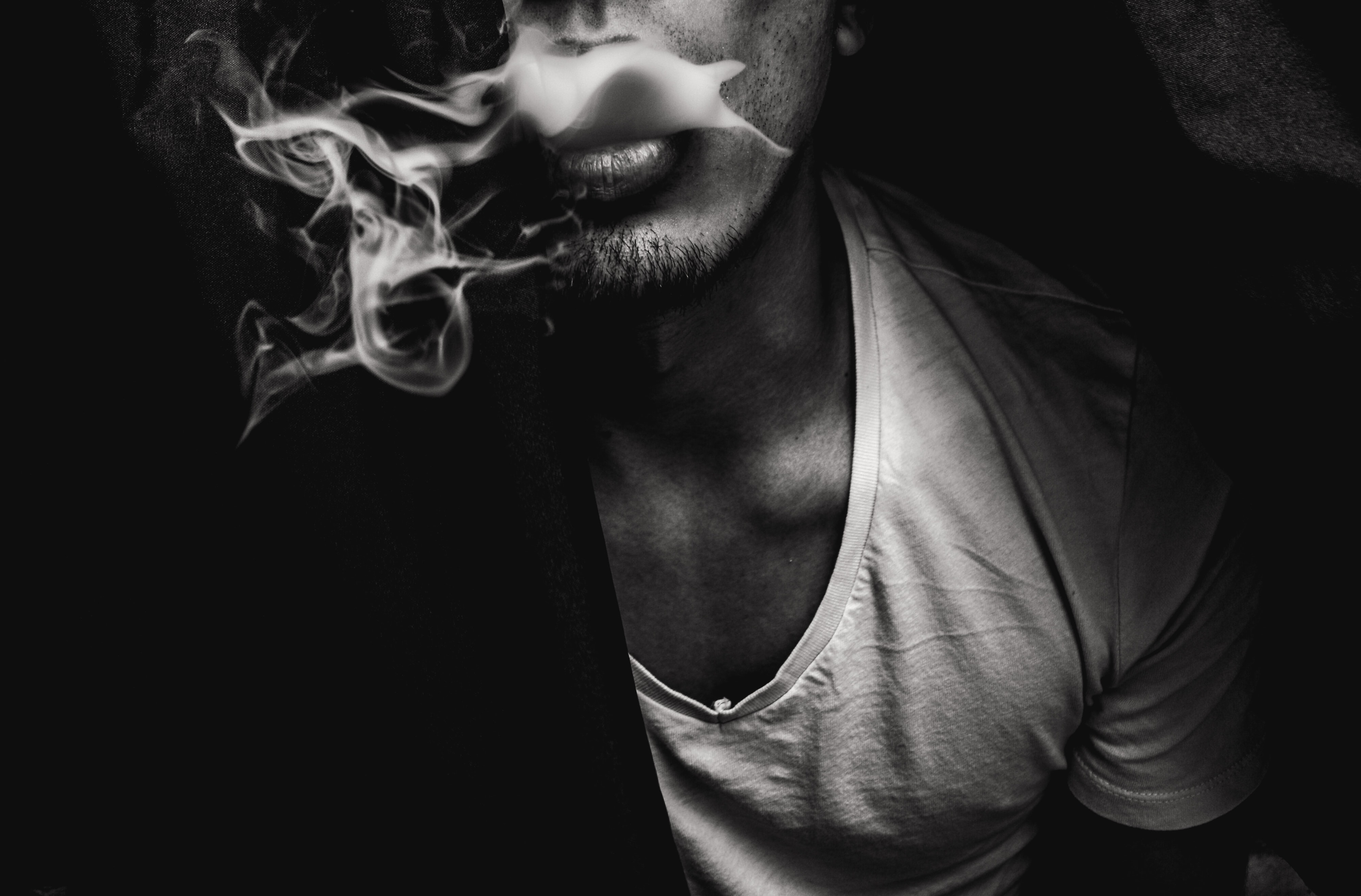man wearing white V-neck shirt with smoke coming out of mouth
