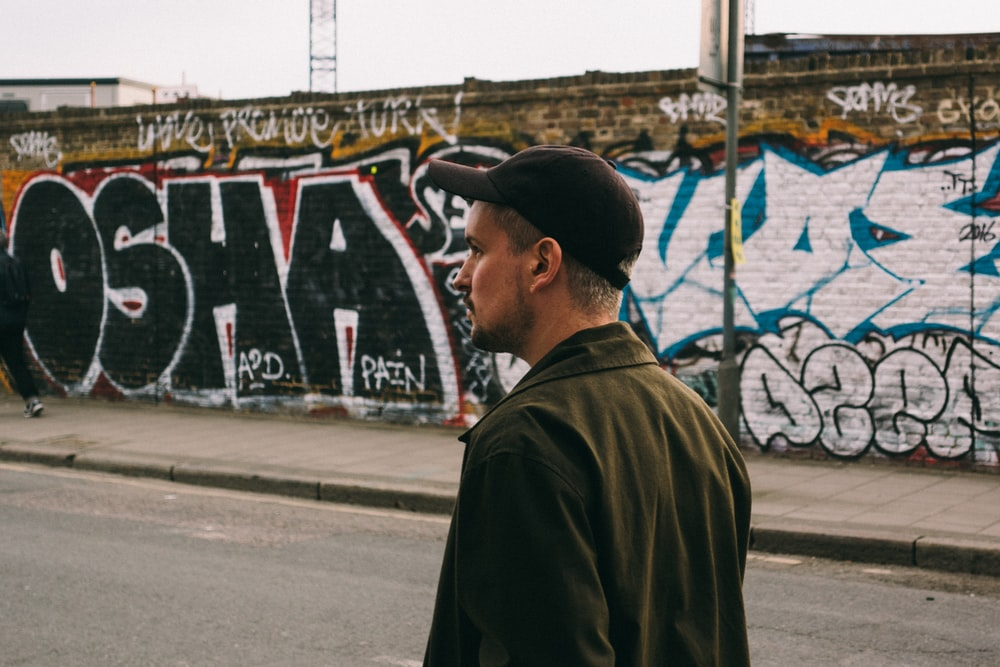 man walking on asphalt road near wall with graffitis