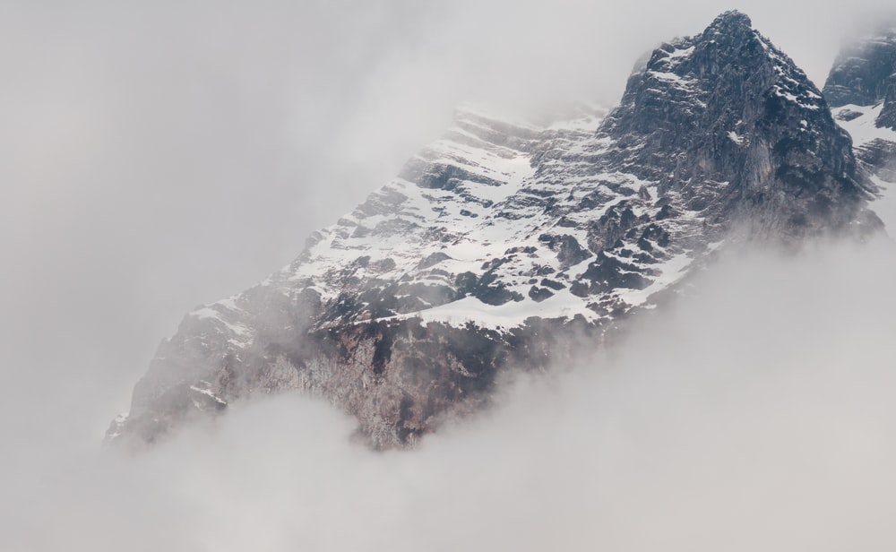 snowy mountain covered by fog