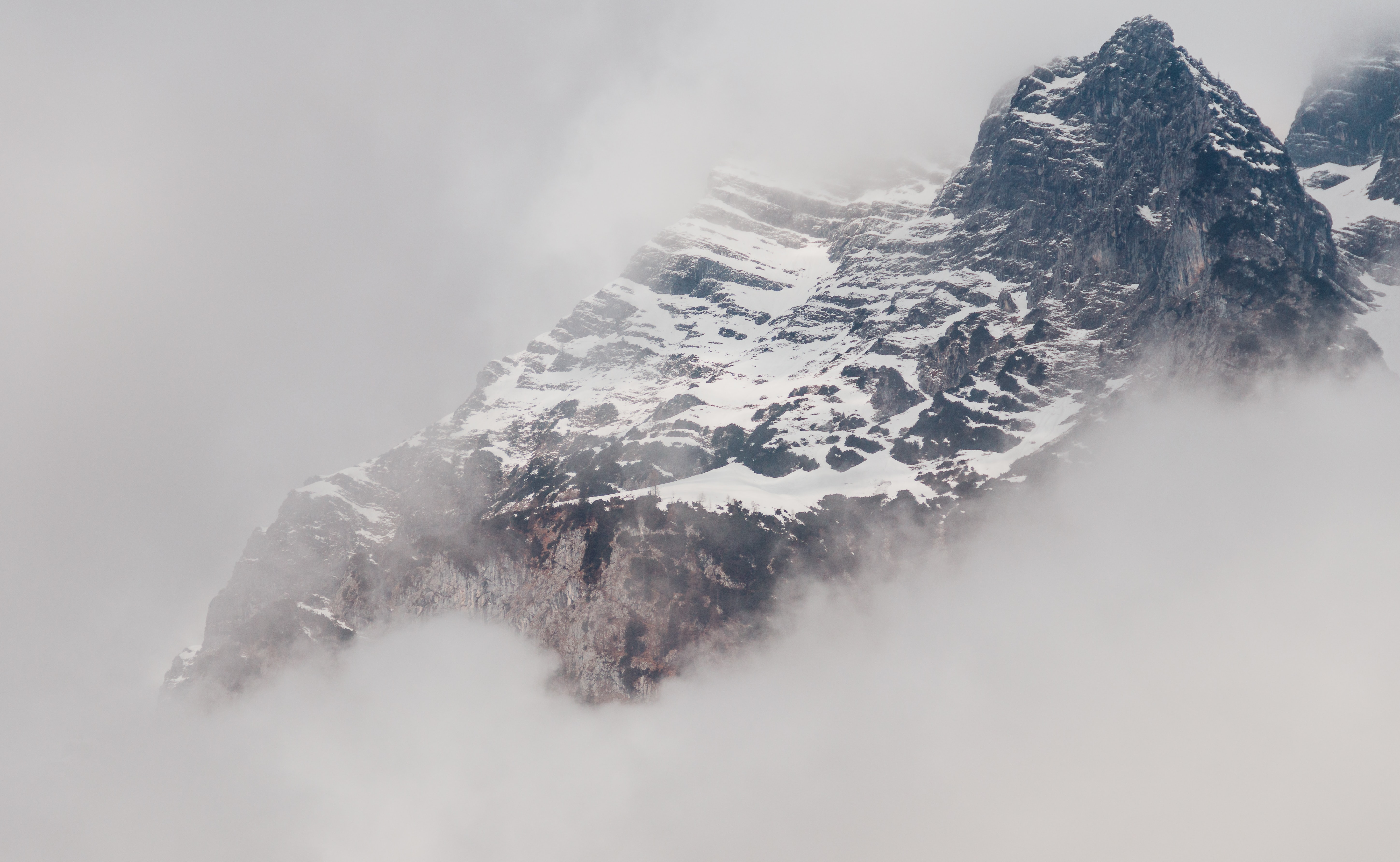 A snowy mountain partially obscured by a thick mist