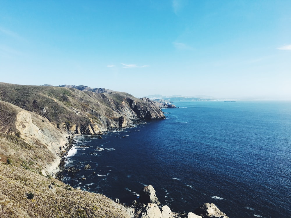 cliff beside ocean under clear blue sky during daytime