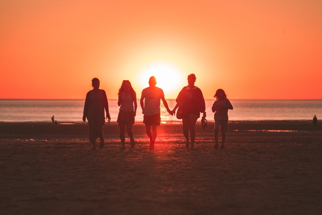 A family at the beach walking into the sea. The sun is setting in the background