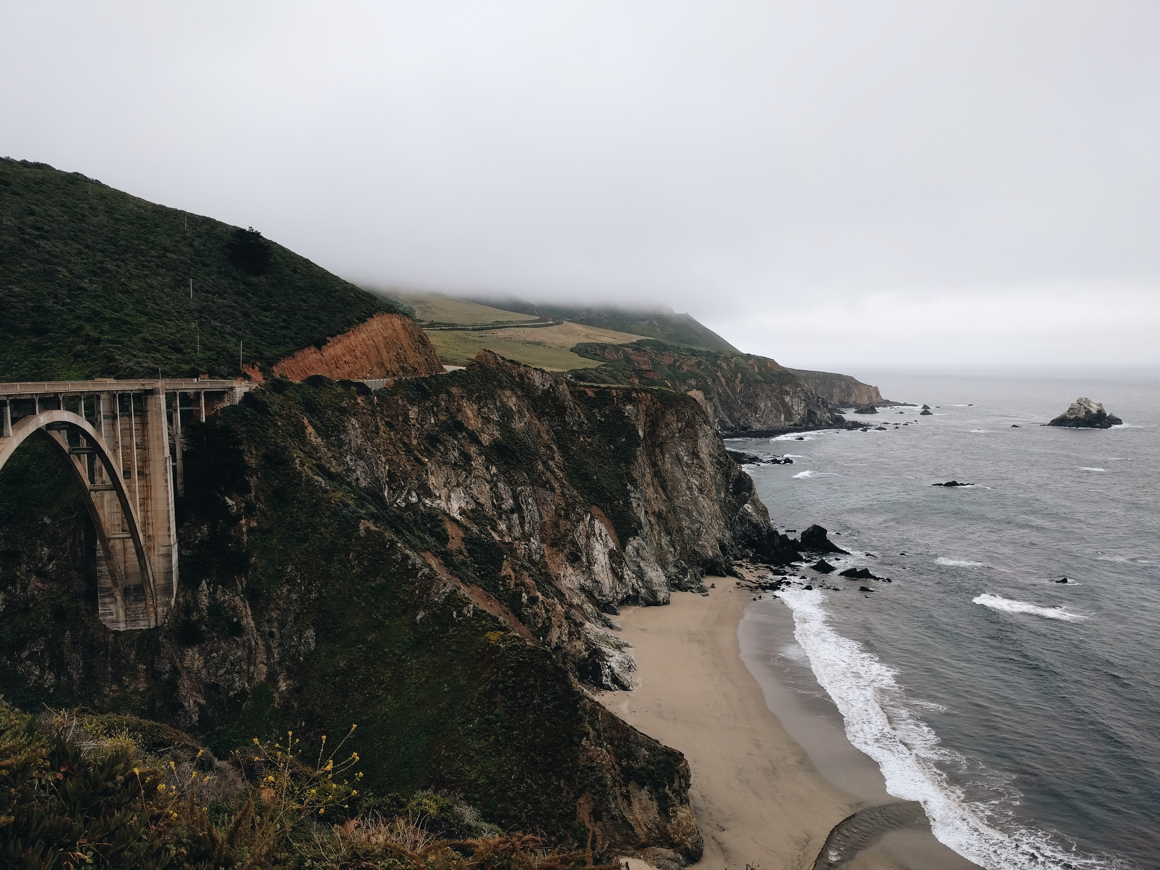 Bridge on the tall rocky shoreline on a cloudy day in Monterey,
