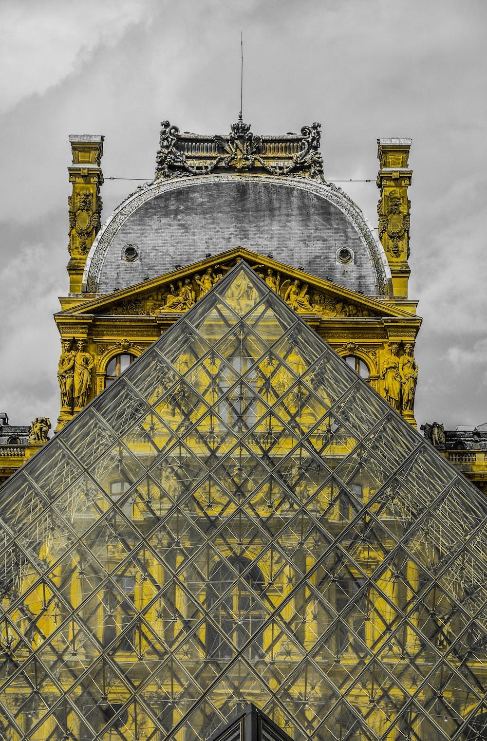 photo of glass triangle-shape building under nimbus cloud