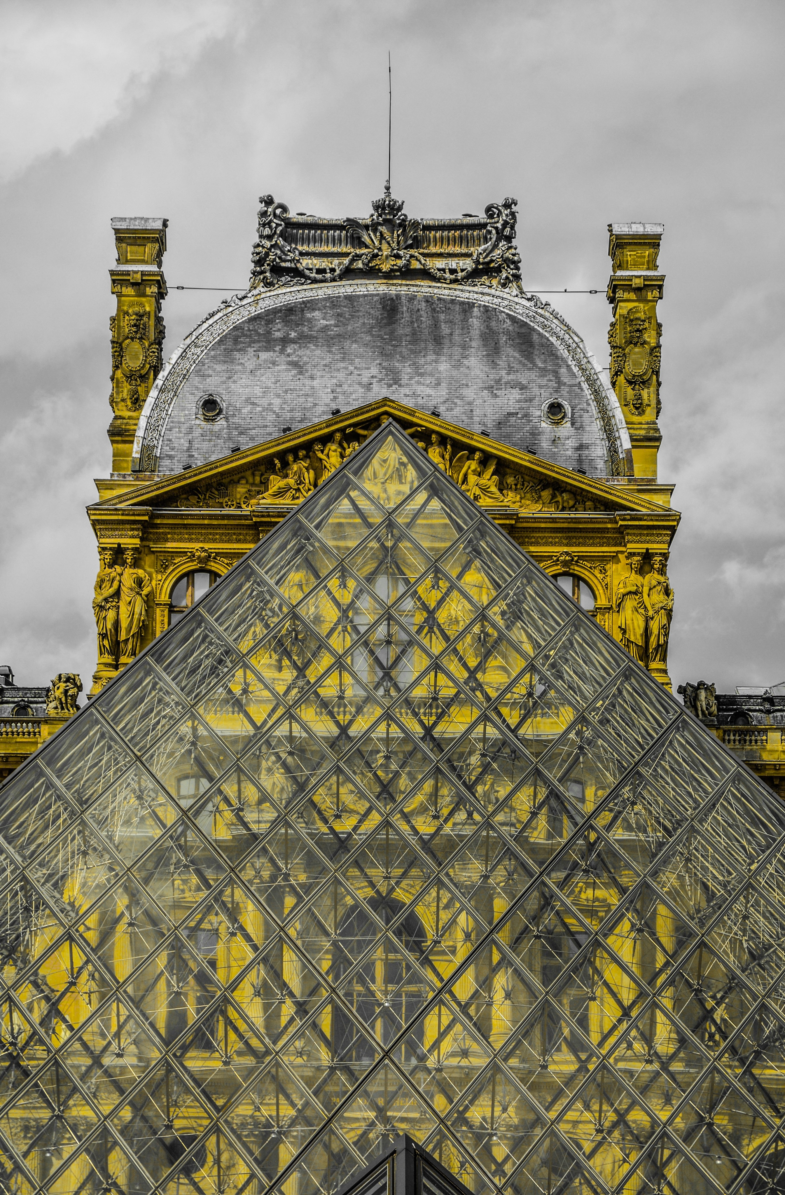 The glass pyramid in front of the Louvre on a cloudy day