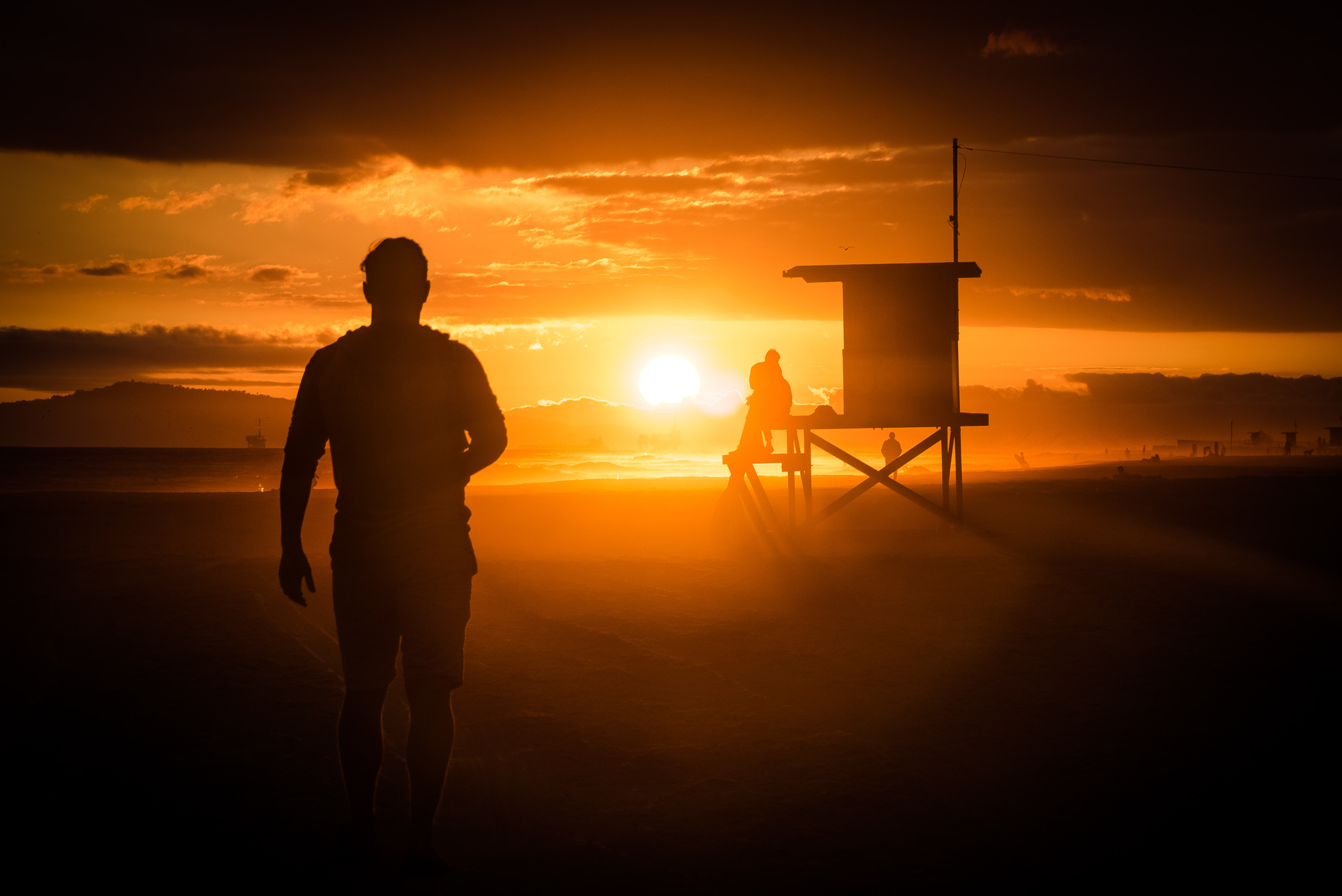 A man walks on Newport Beach with a low sunset casting the lifeguard hut into silhouette.