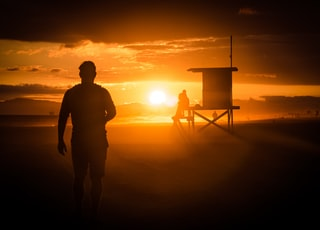 silhouette of man standing near wooden shed during sunset