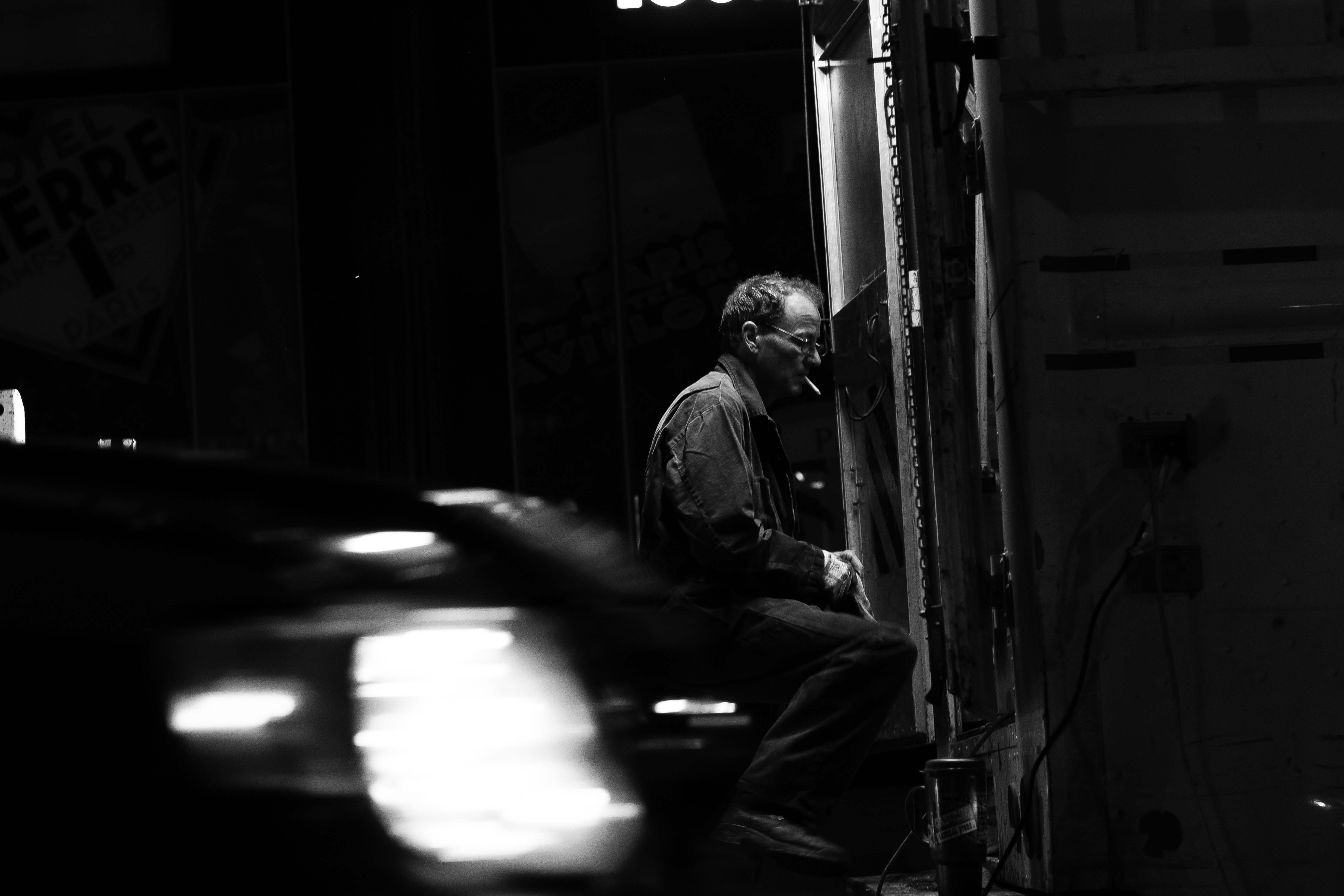 A man in black-and-white sits operating a machine against a blurry background