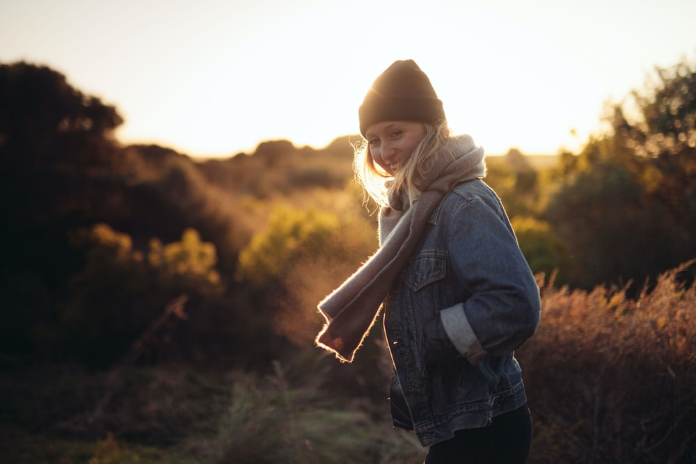 smiling woman taking photo near trees and brown grass during sunrise