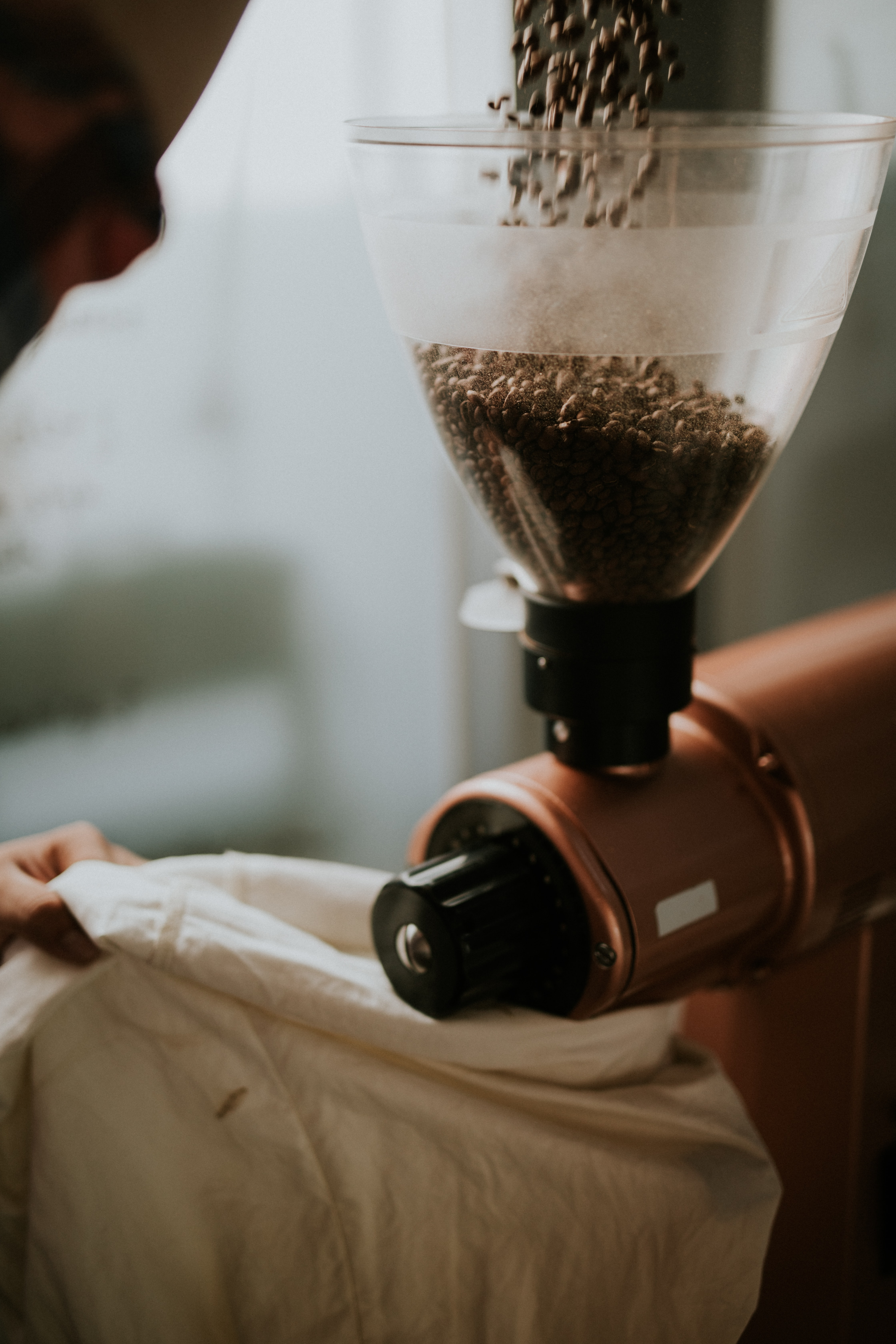 Pouring coffee beans into a grinder in a cafe kitchen