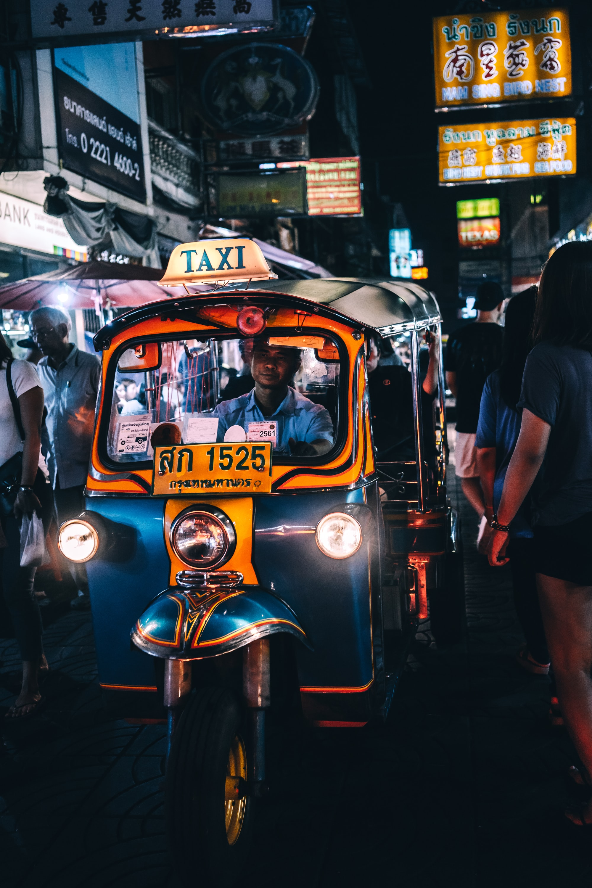 A Tuk-Tuk driver makes his way through a crowd in the busy Chinatown area of Bangkok, Thailand.