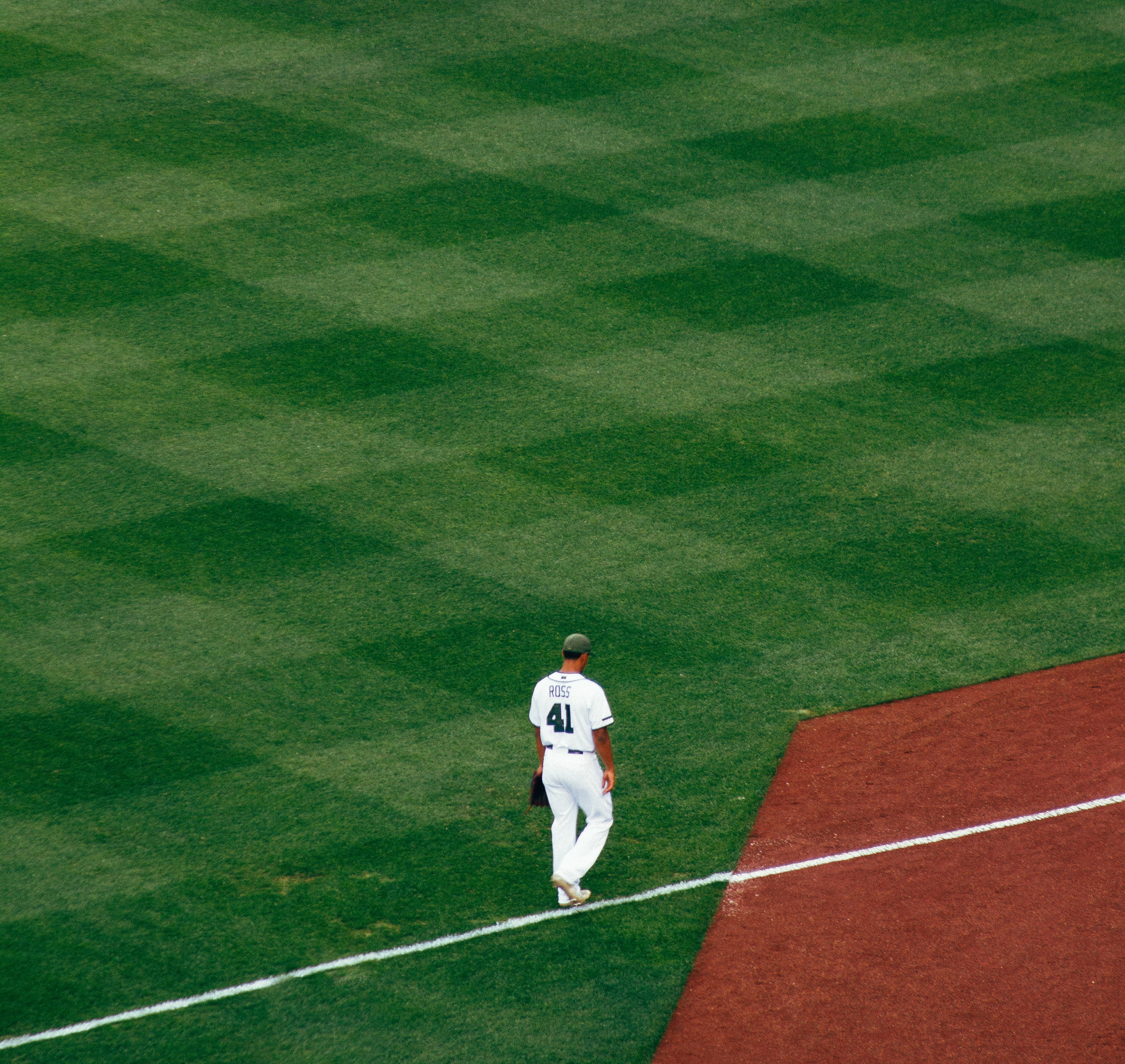 baseball player standing on field steps on white line at daytime