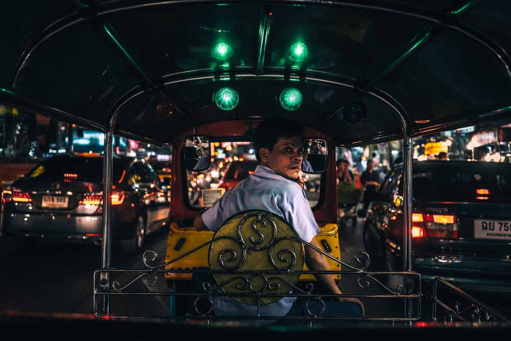 man in white collared shirt sitting in yellow and black autorickshaw between cars with taillights turned on at night