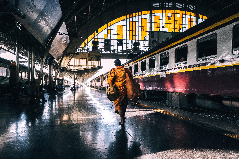man walking on railway station platform near train