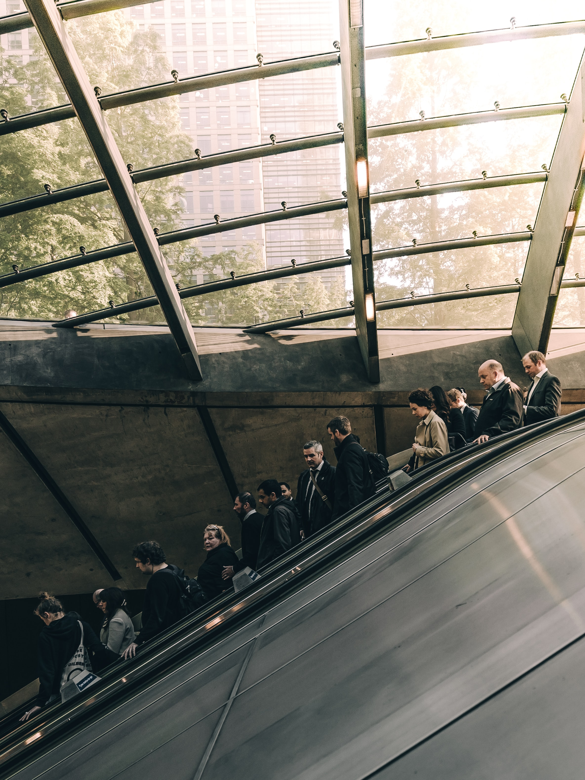 A line of people in business attire on an escalator in Canary Wharf