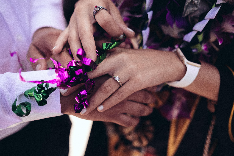 Newlywed couple interlocking hands during ceremony
