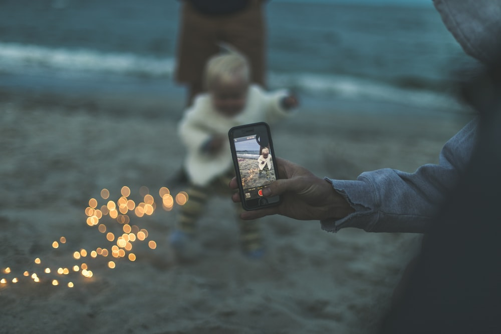 person using smartphone capturing baby on brown sand