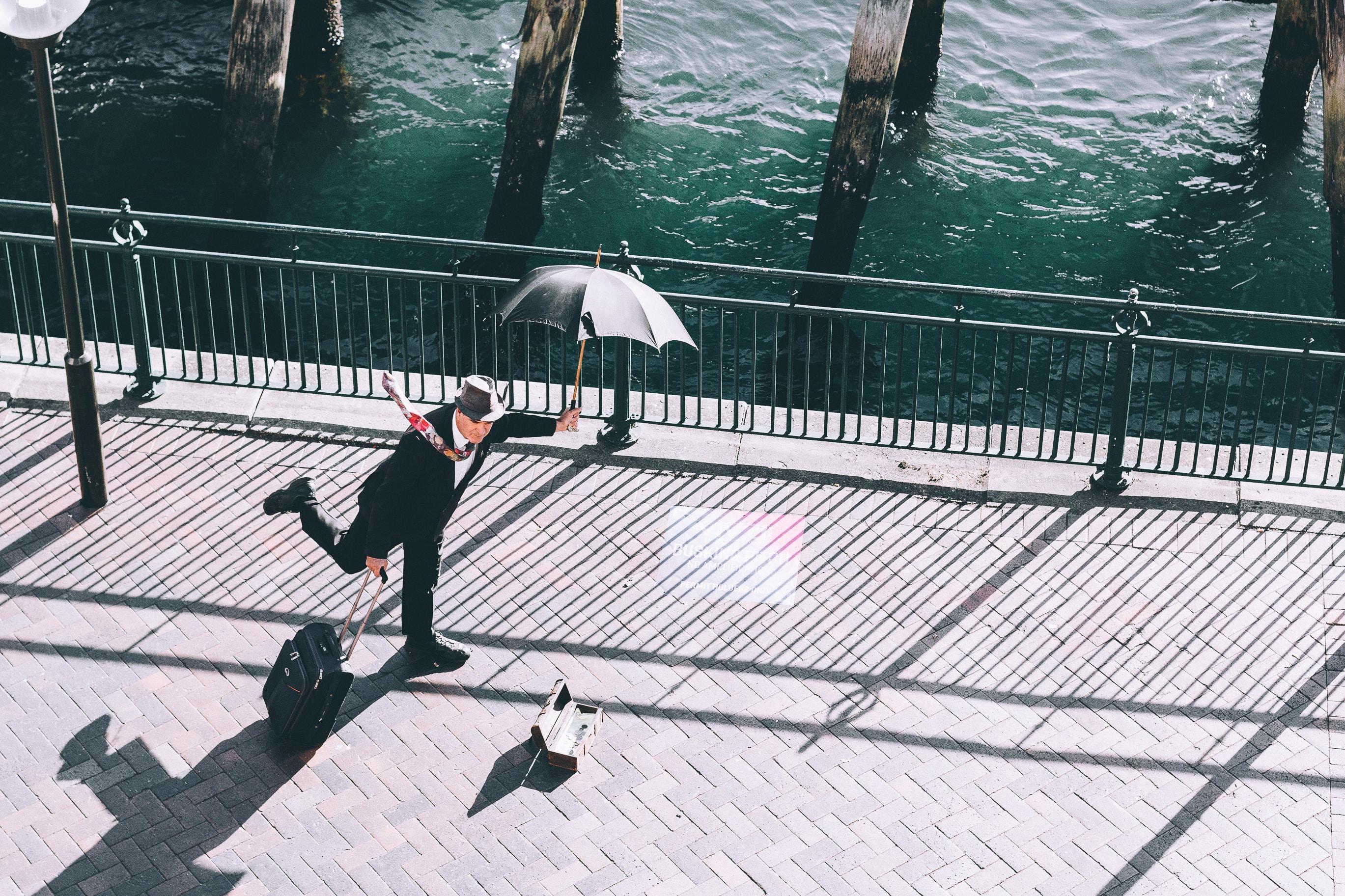 man holding umbrella and trolley bag on bridge