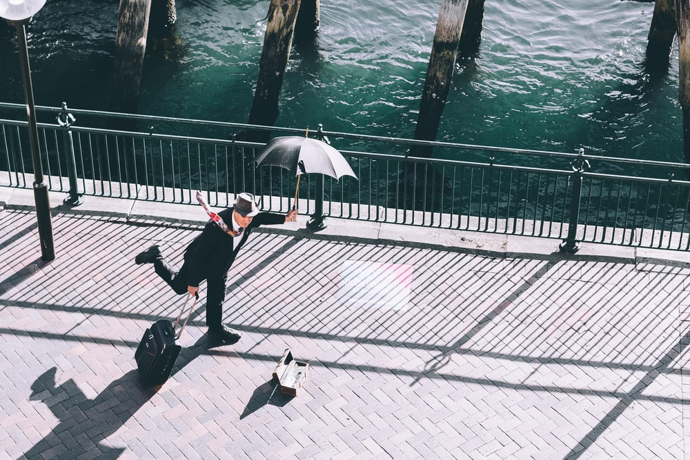 man holding umbrella and trolley bag on bridge