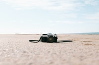 black and silver SLR camera on seashore
