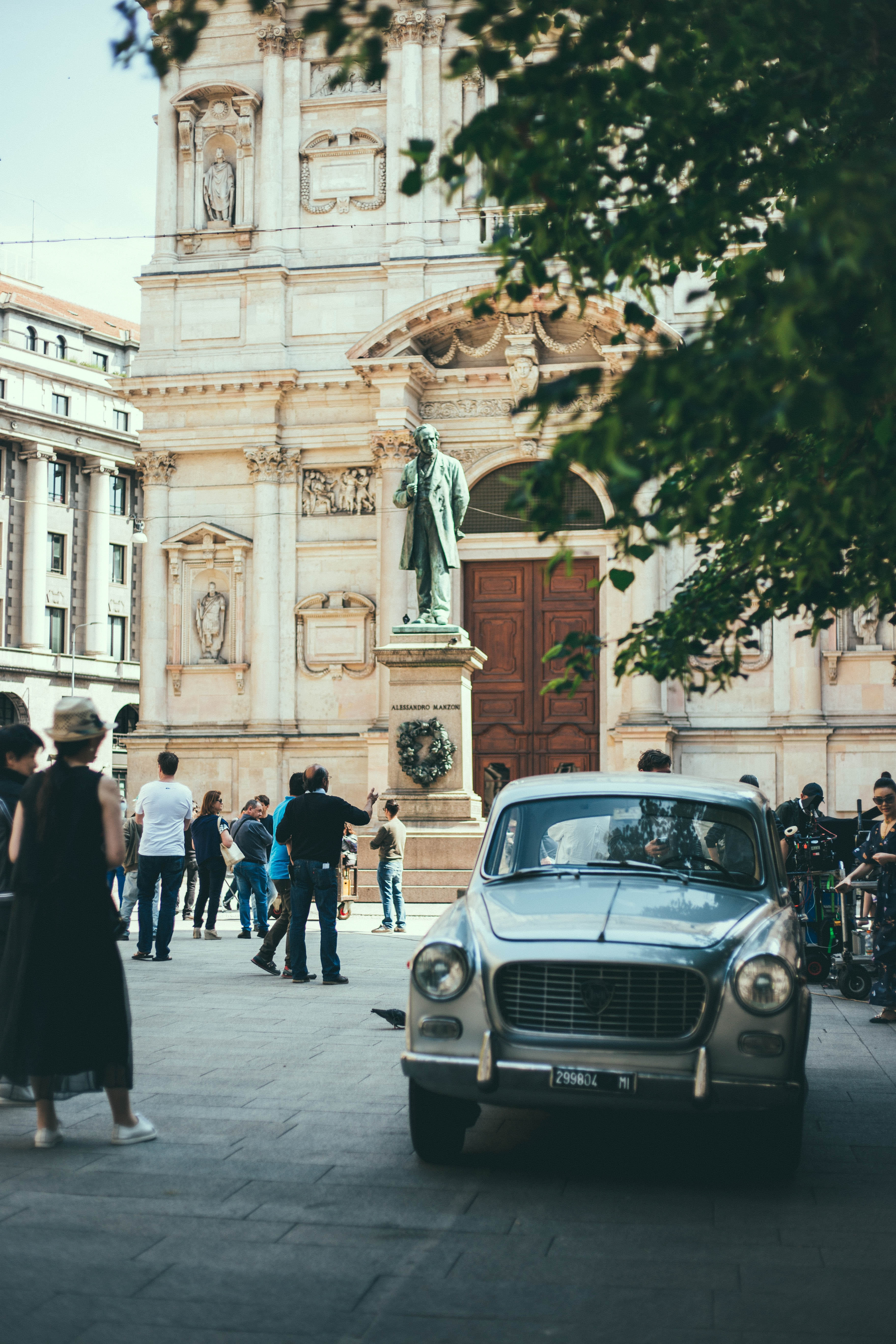 Old vintage white car parked on the crowded square in front of the statue and an old building in Milan