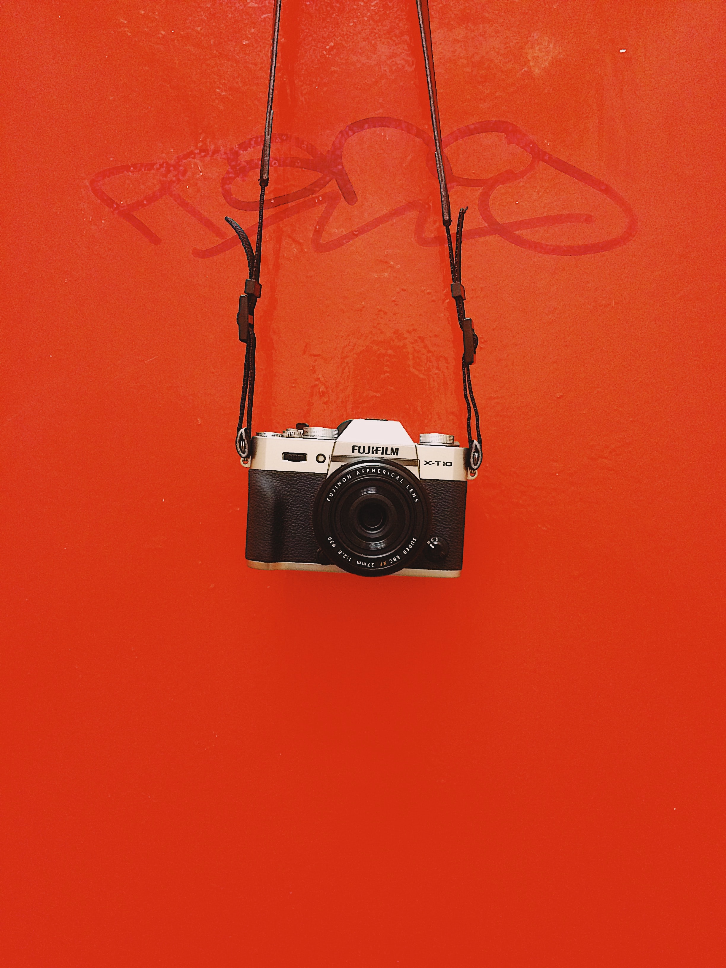 Black Fujifilm camera and straps in front of red surface with graffiti