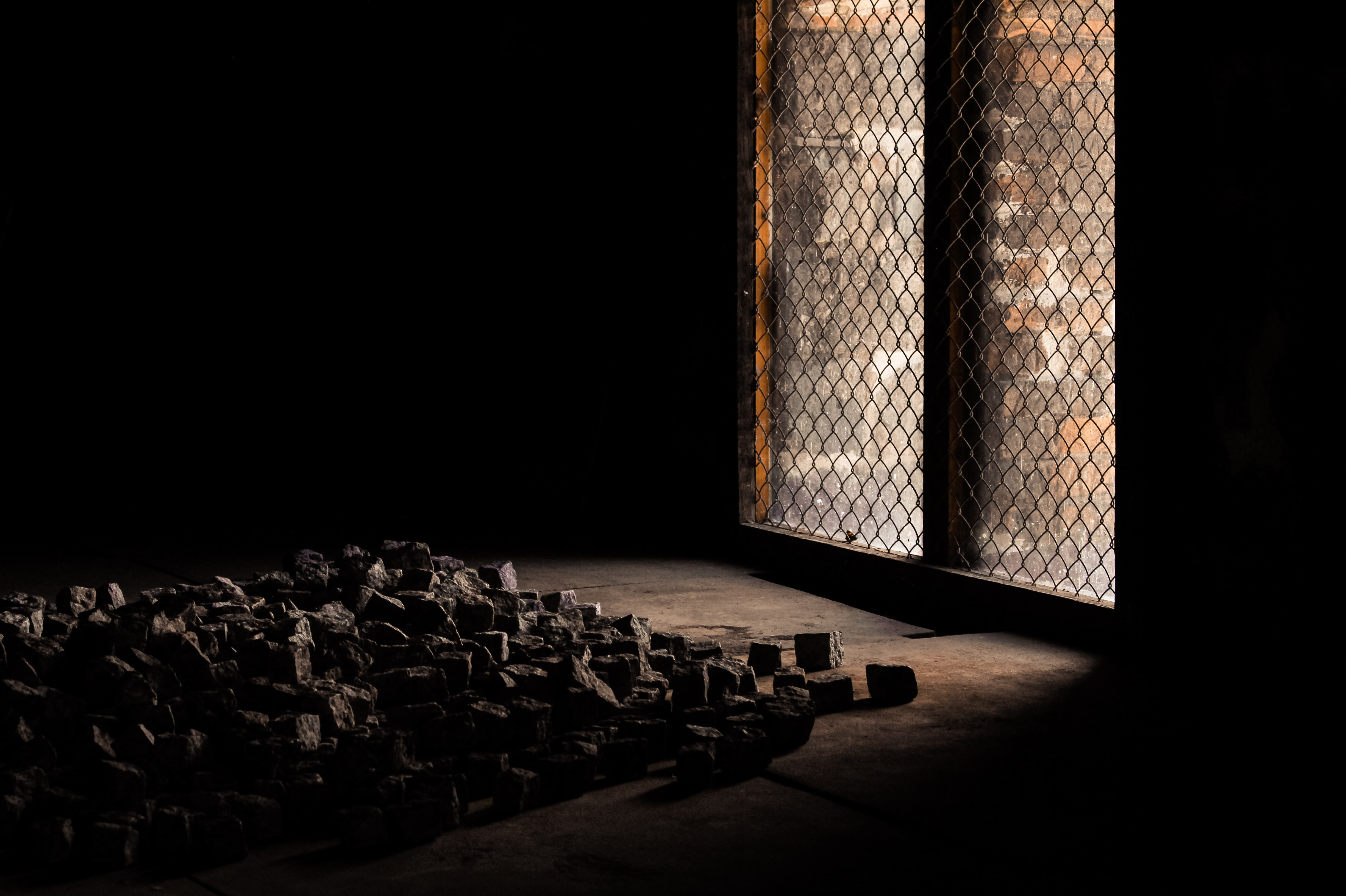 Interior of a dark room with bricks on the floor and light entering through a window