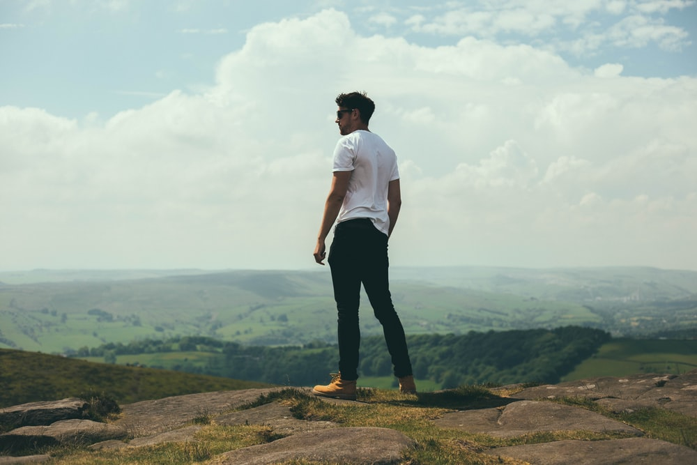 man standing on bolder overlooking the hills and mountains
