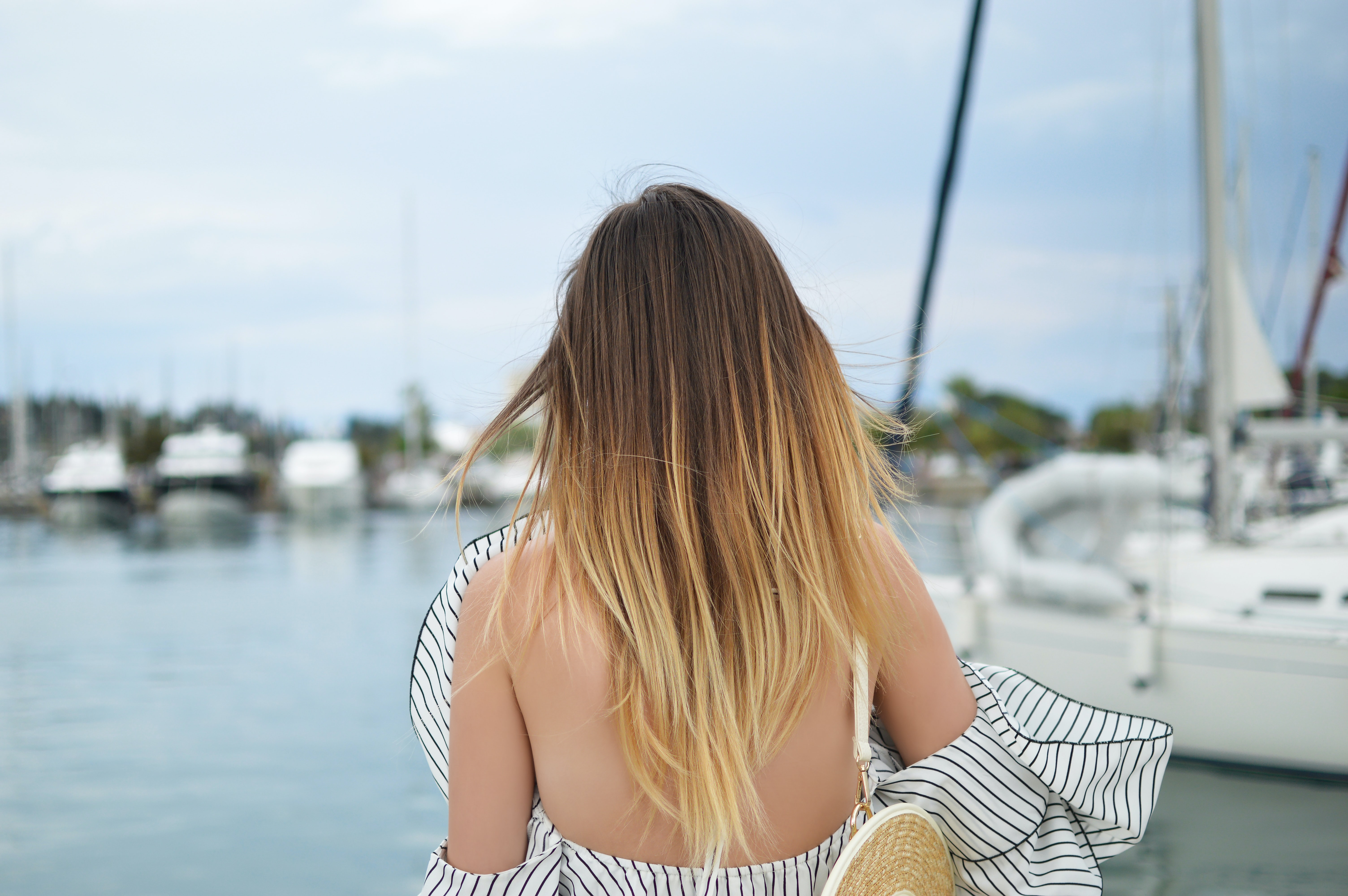 Standing behind a woman in a chic striped dress near yachts