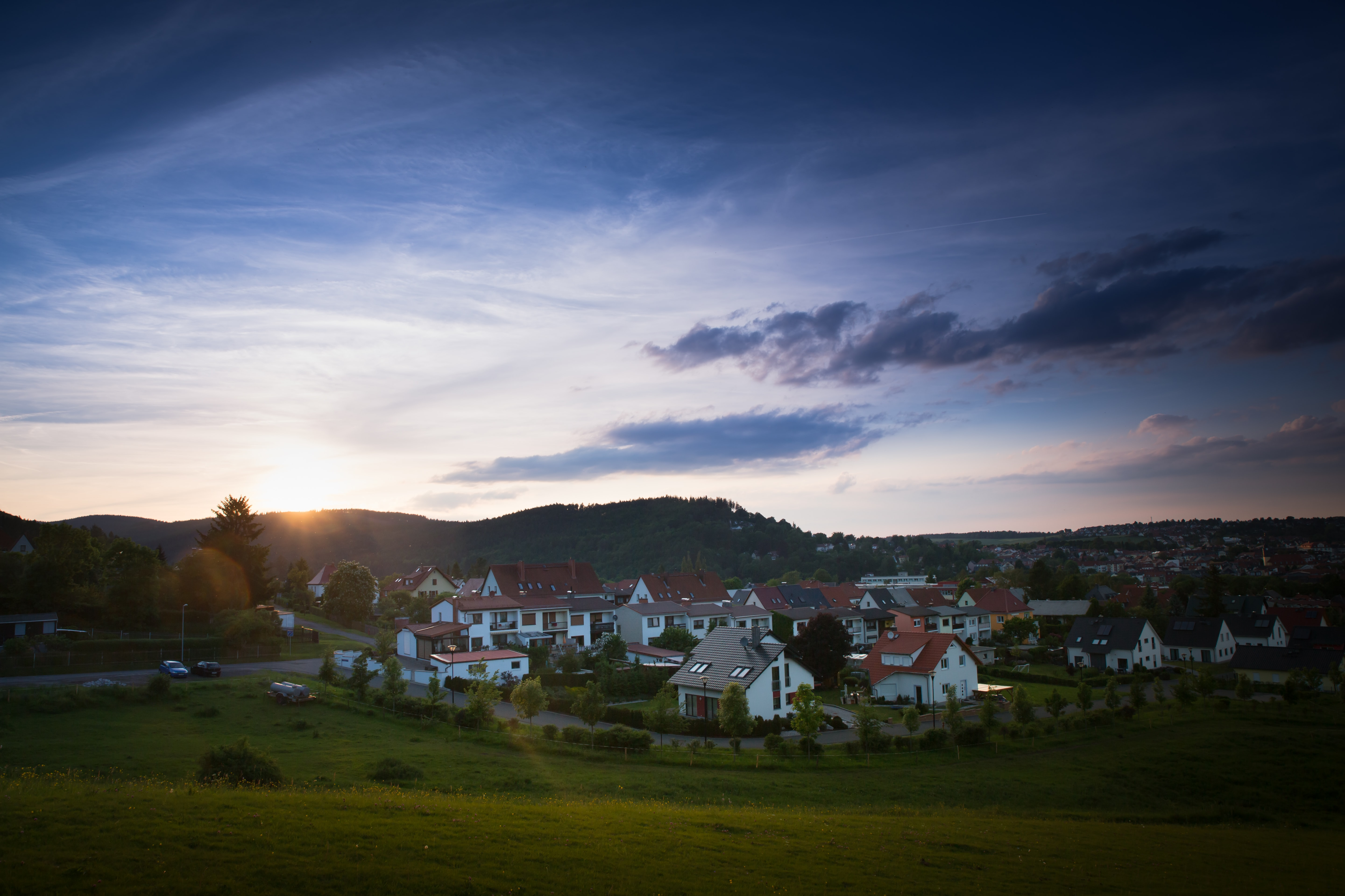 houses on green grass field under cloudy sky during daytime