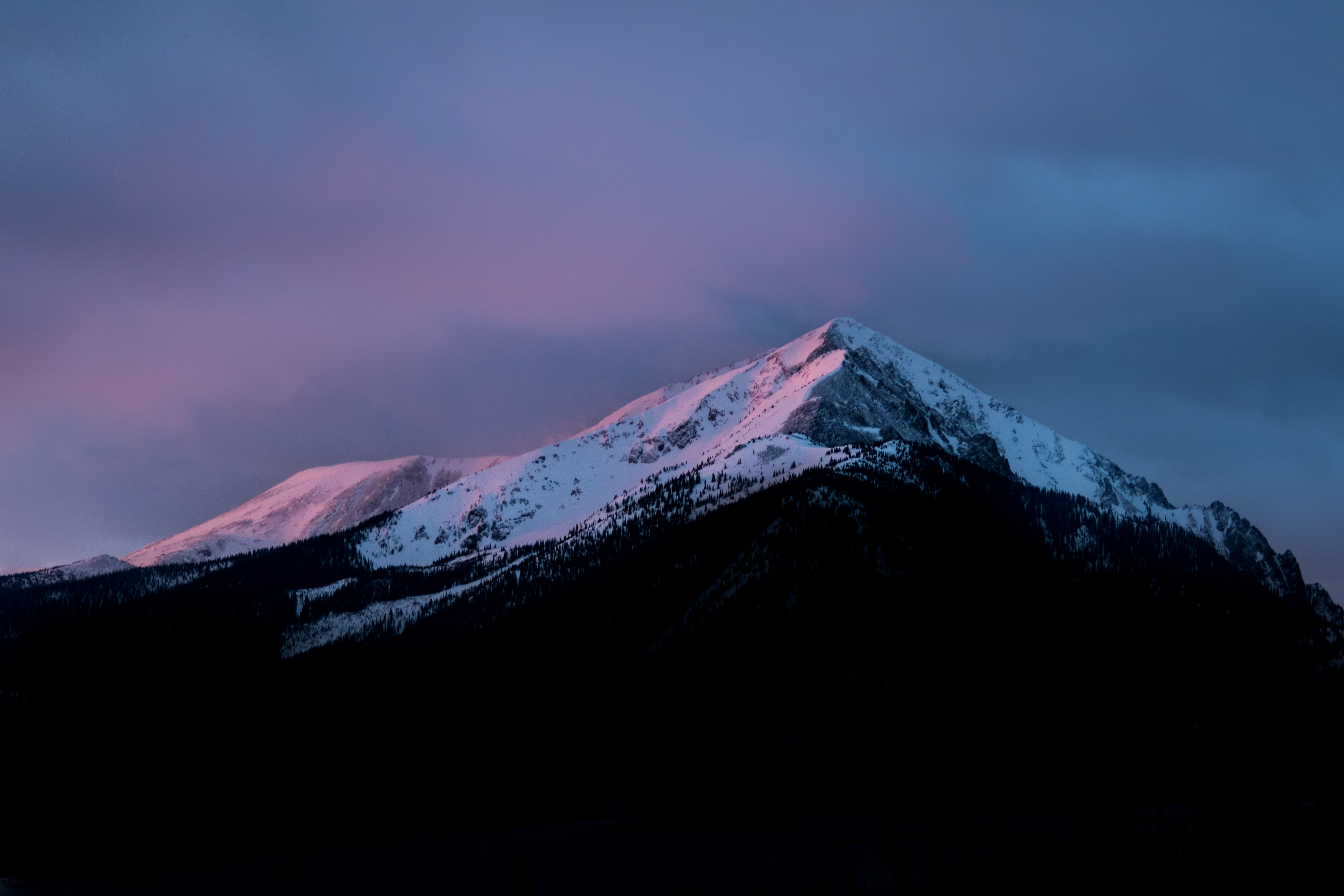 A sharp snow-capped mountain peak in Silverthorne during dusk