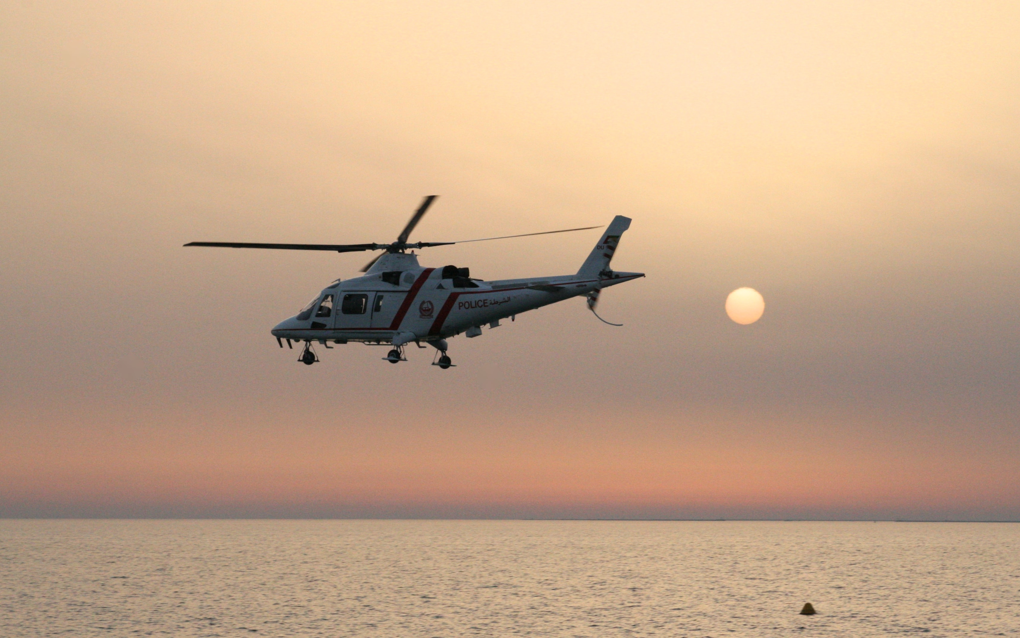 A helicopter flying over the water during sunset.
