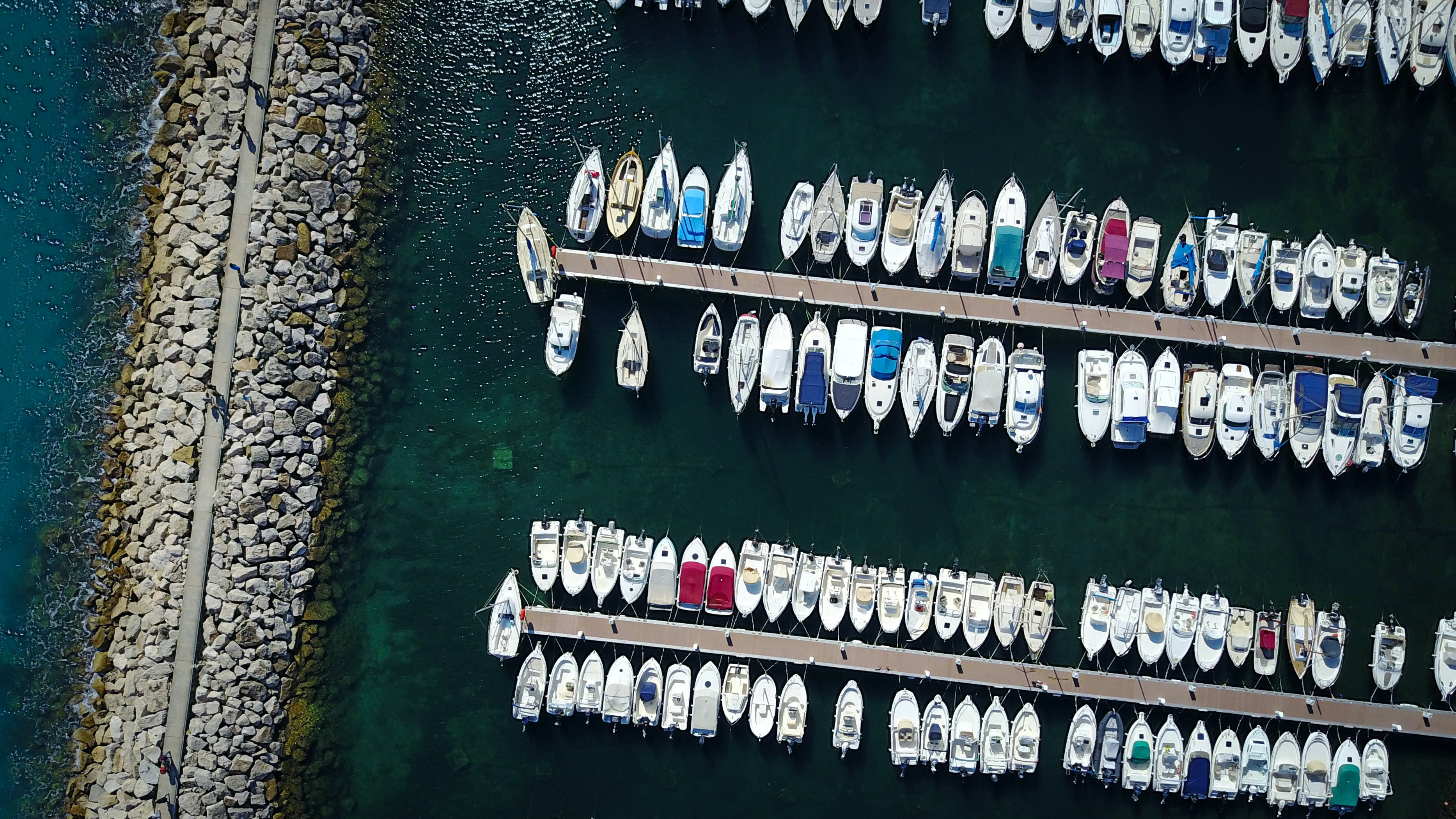 A drone shot of boats moored at a marina in Marseille