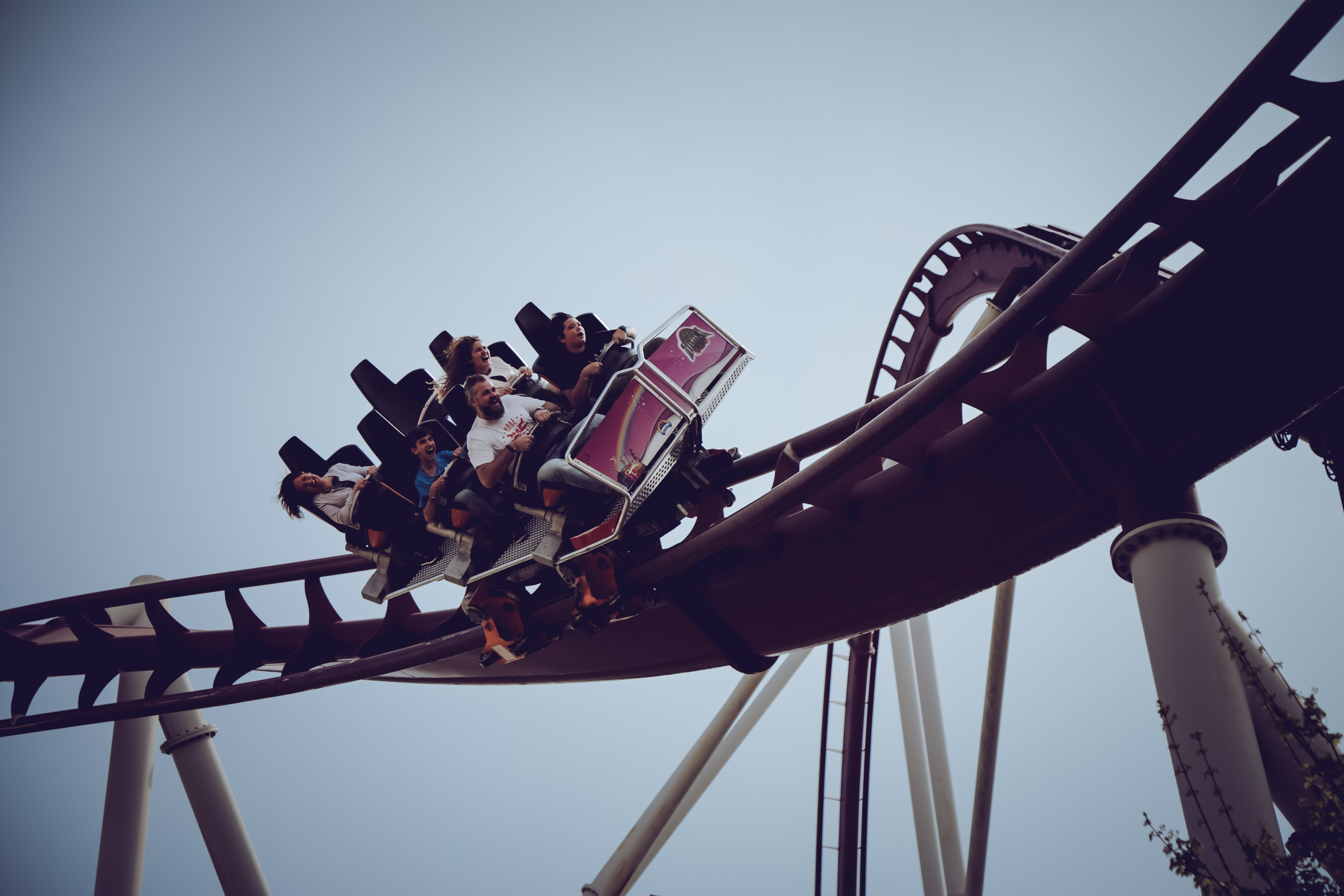 People enjoying themselves on a small rollercoaster in an amusement park