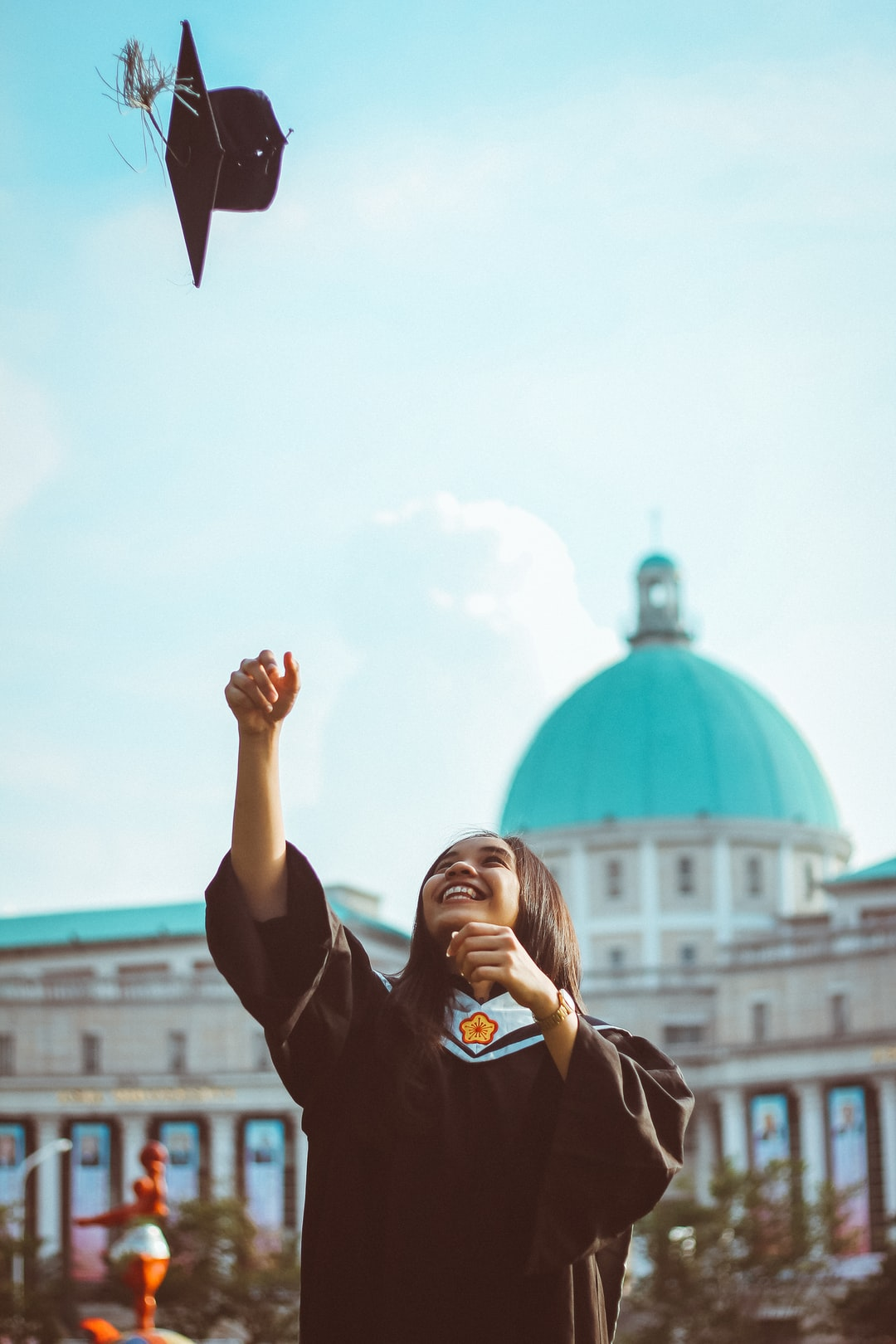Woman graduate smiles as she throws cap up in the air with Asia Museum of Modern Art in background