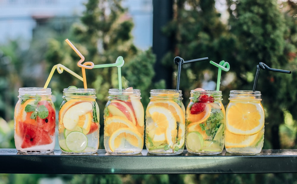 six clear glass mason jars filled with juice on black table