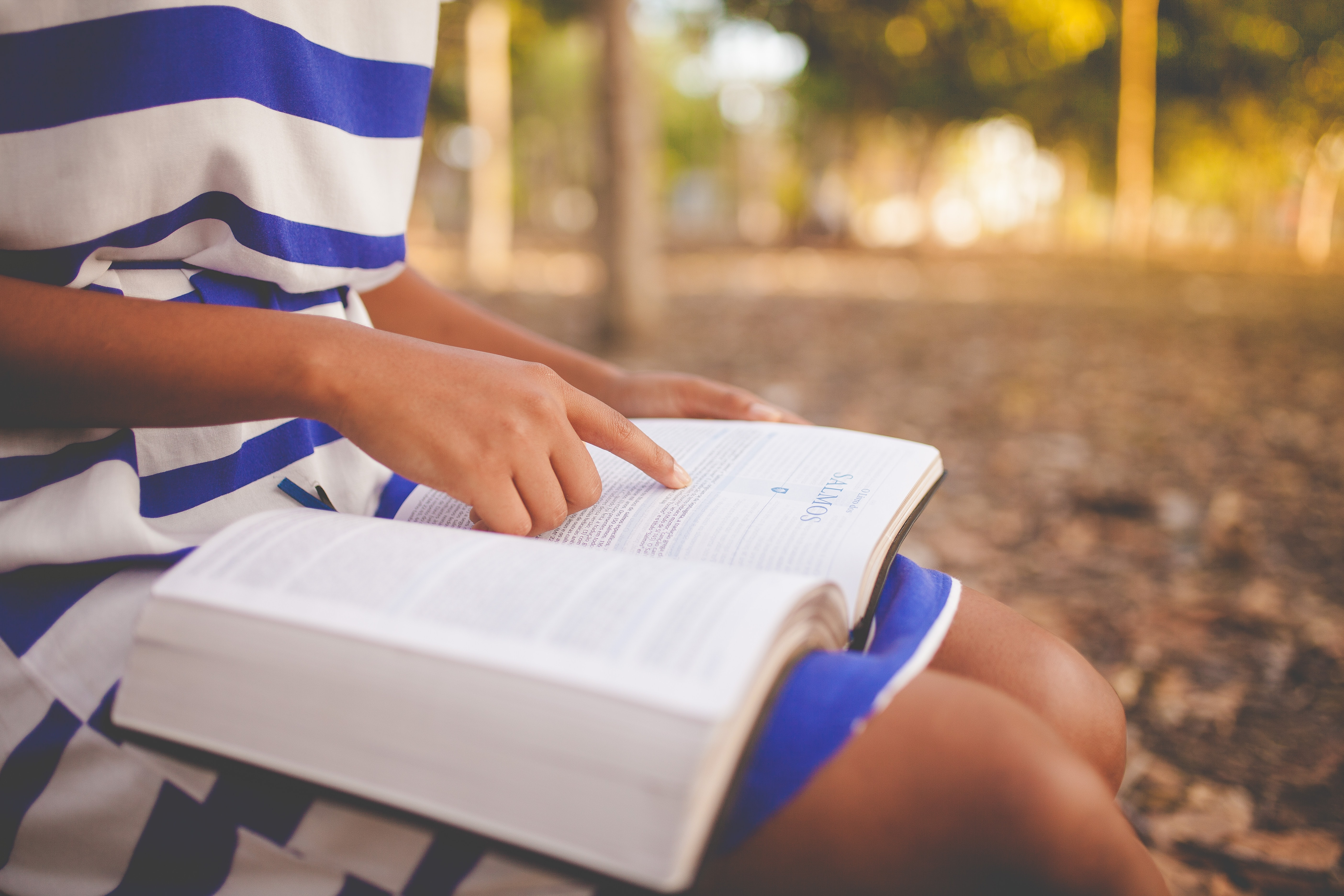 A woman in a blue and white striped dress sitting in a park reading her book.