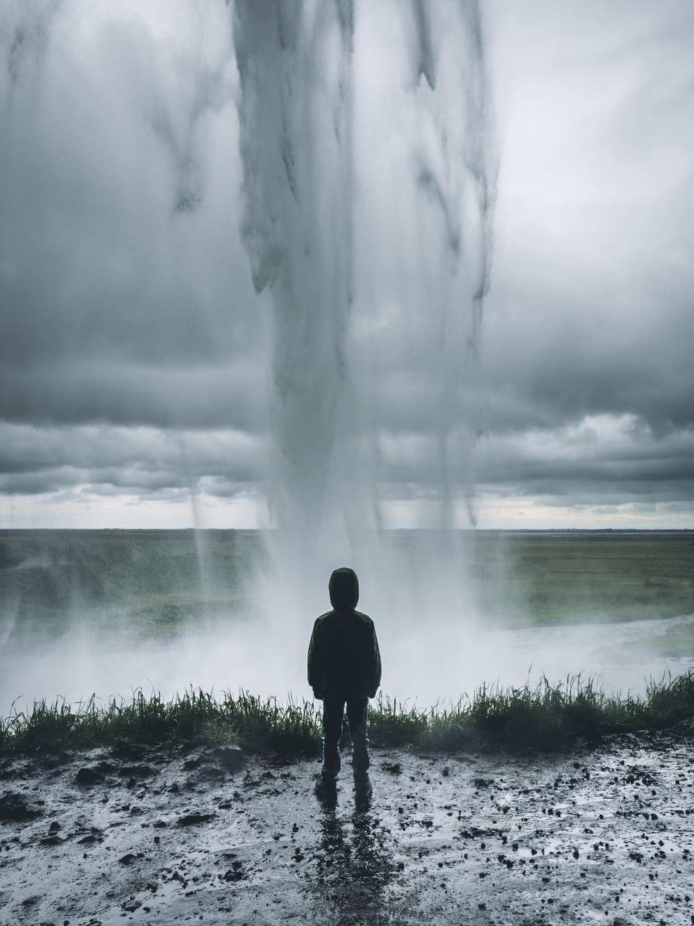 toddler standing in front of water formation
