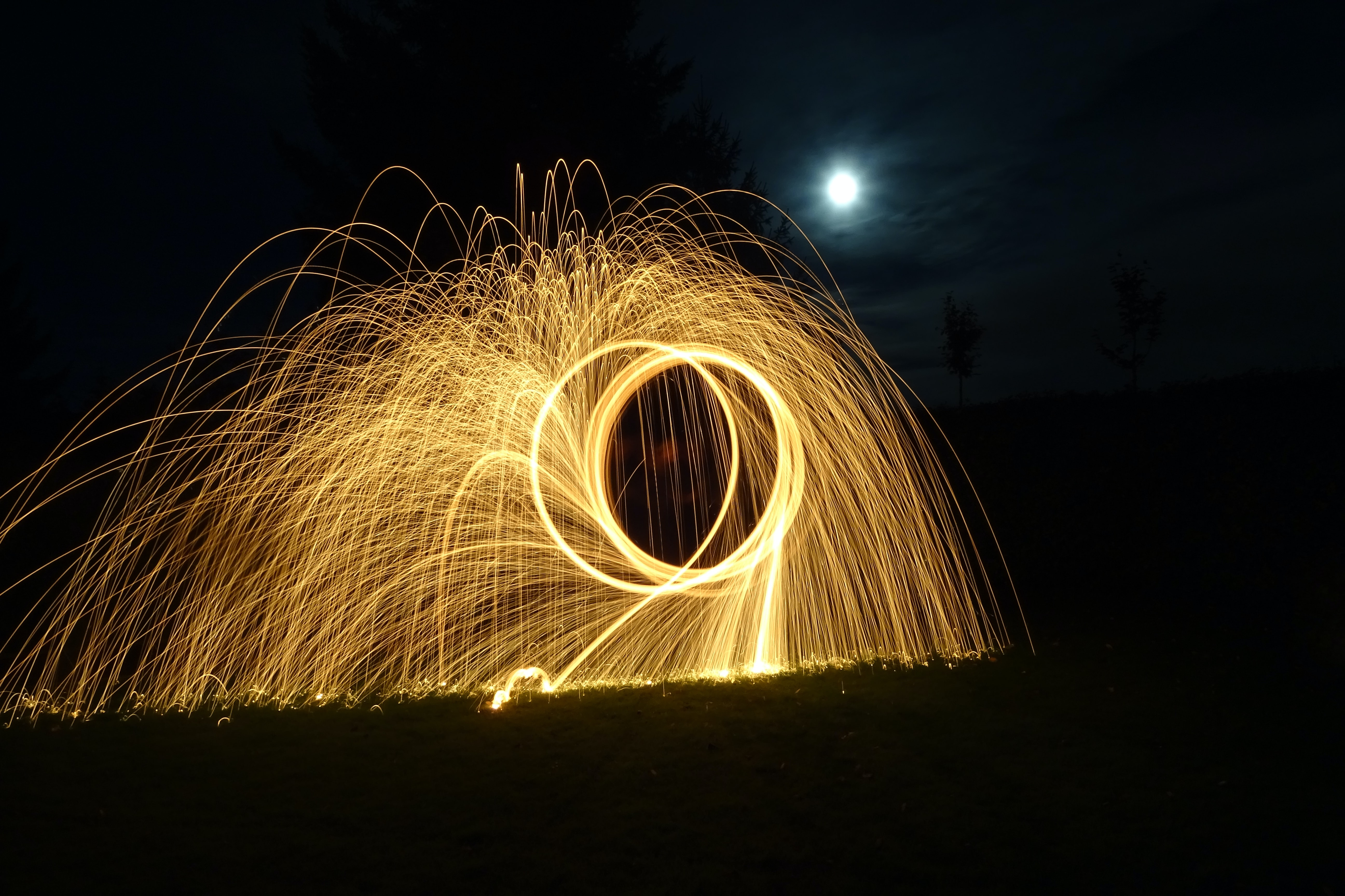 Light trails caused from long exposure simulating a hoop shape and fireworks in a dark moonlit night