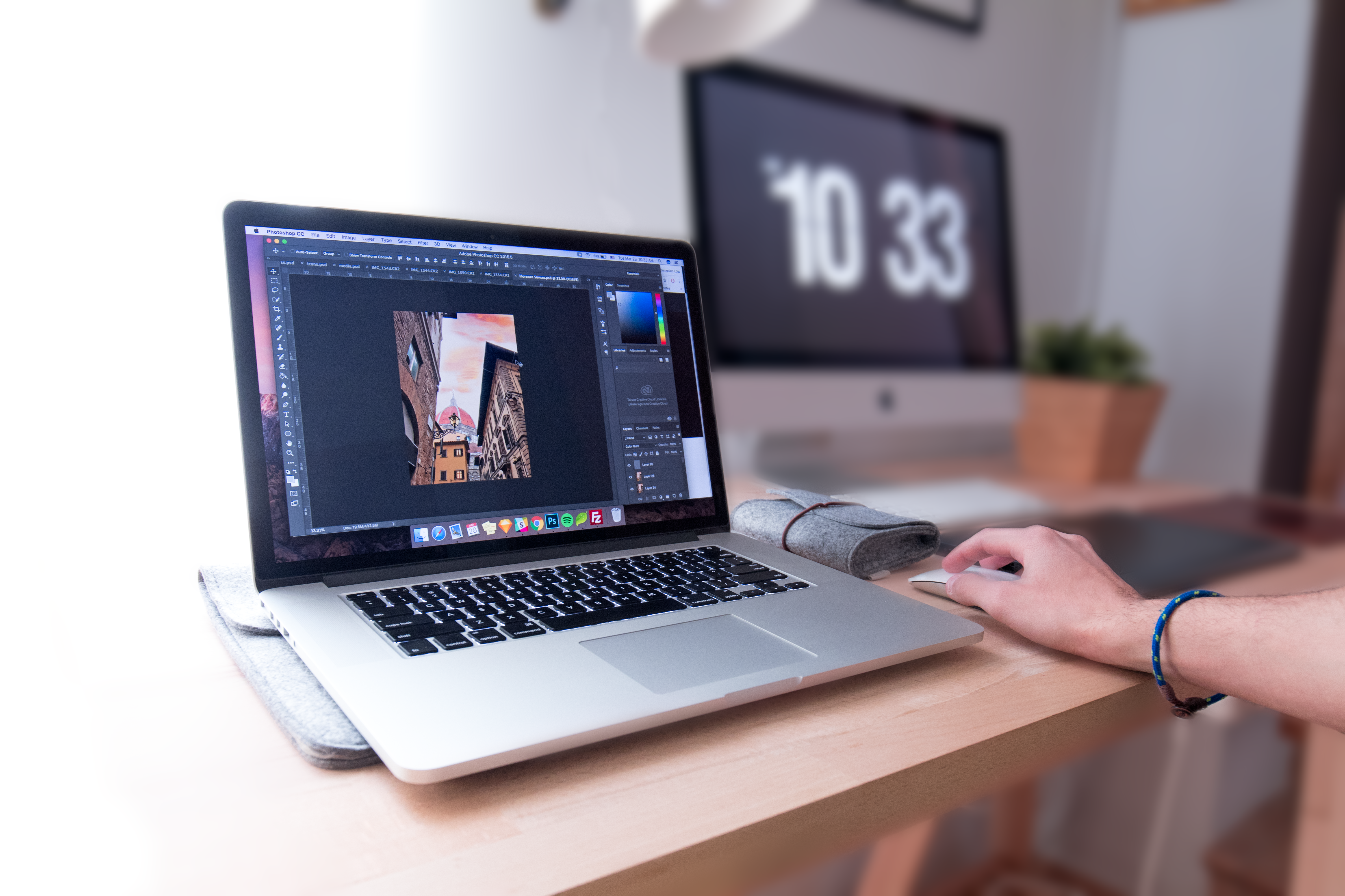 A silver Macbook laptop with Photoshop running sits on a wooden desk while a person's hand is using the mouse